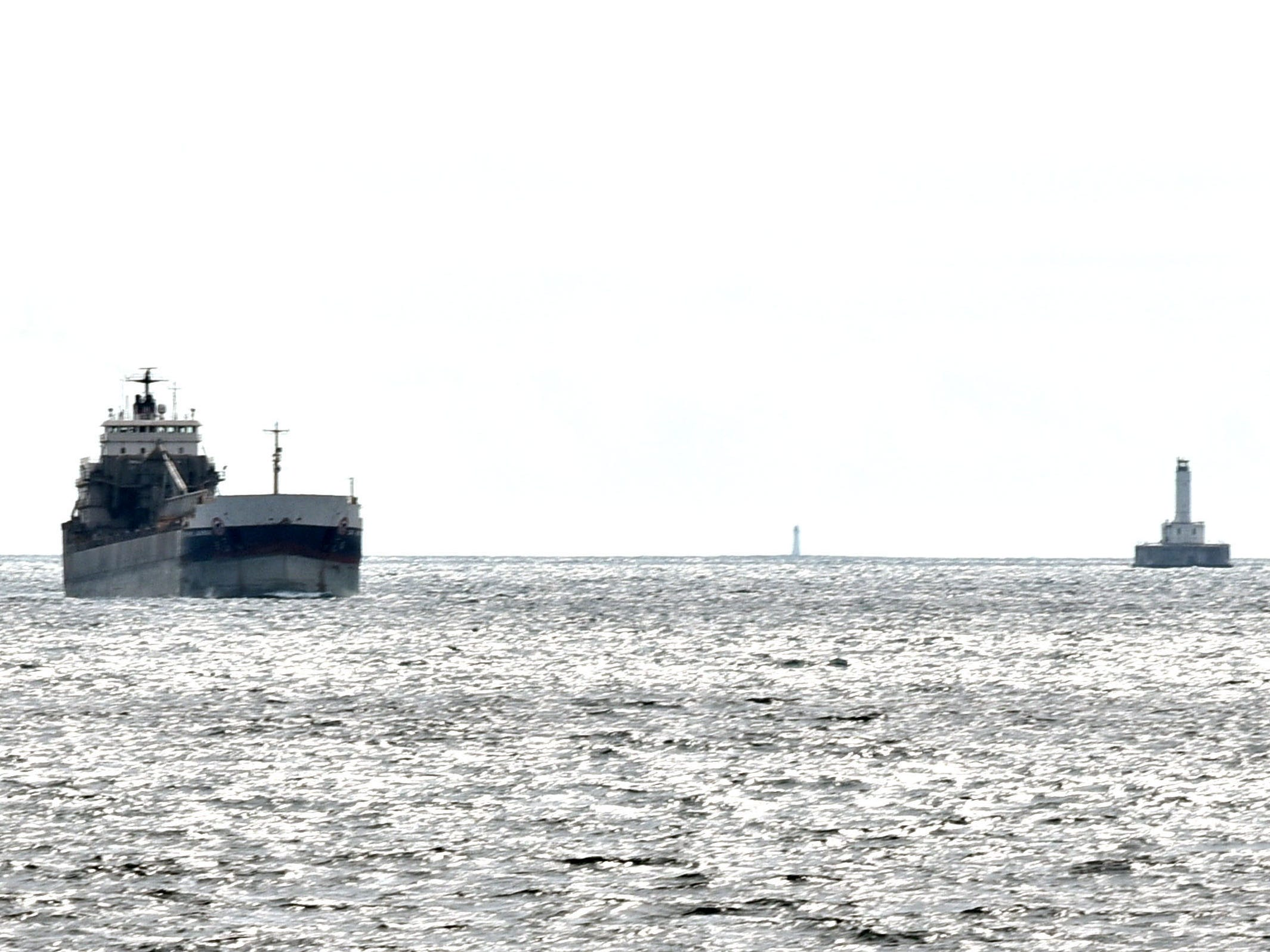 The Canadian bulk carrier Capt. Henry Jackman rounds Gray's Reef Light headed toward the White Shoal Lighthouse Sunday, Sept. 2, 2018, sailing toward the Straits of Mackinac. The northern shippiing lanes are littered with shallow,  dangerous shoals, marked by several century-old lighthouses to aid in navigation.