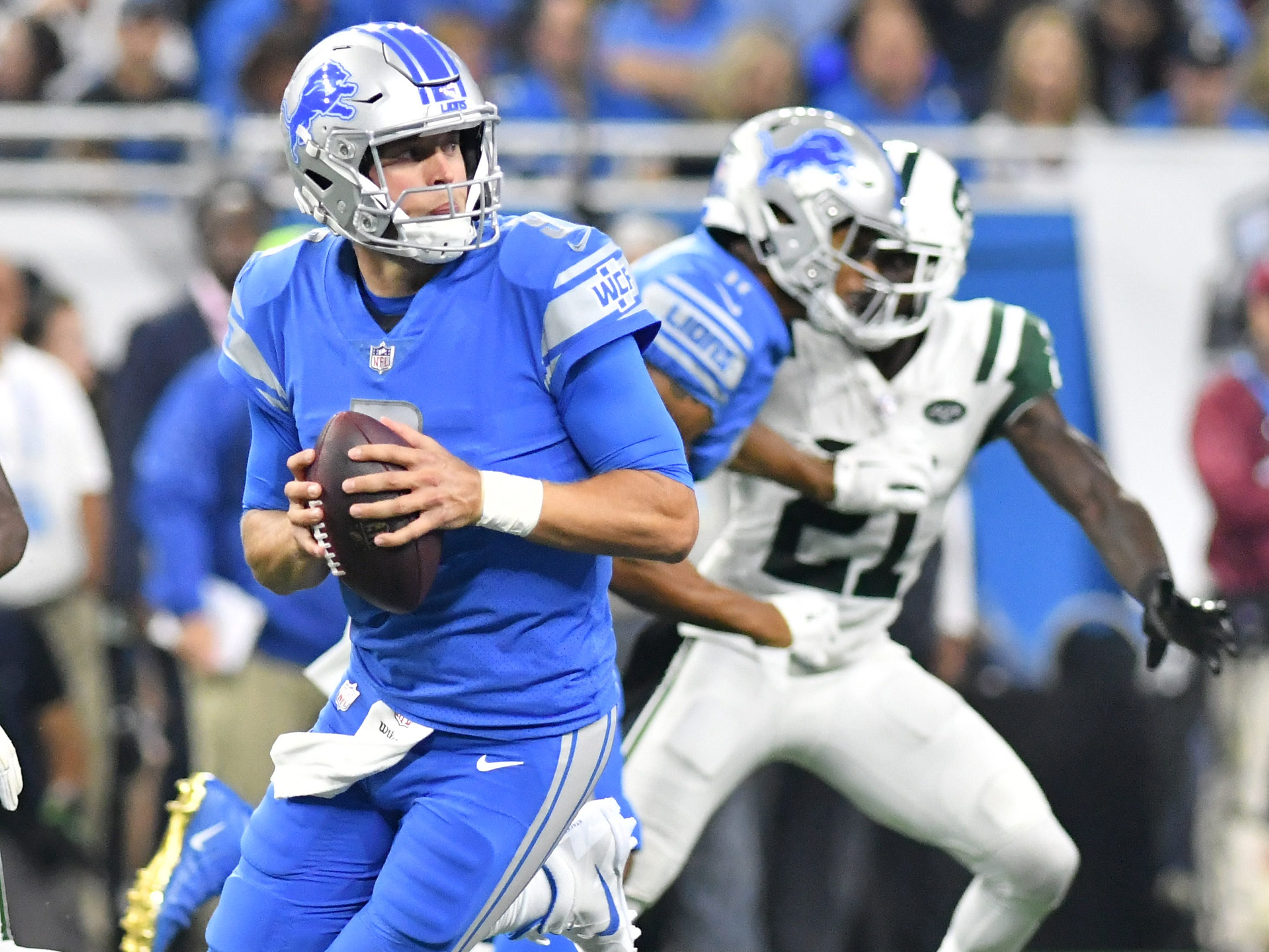 Lions quarterback Matthew Stafford scrambles in the first half.