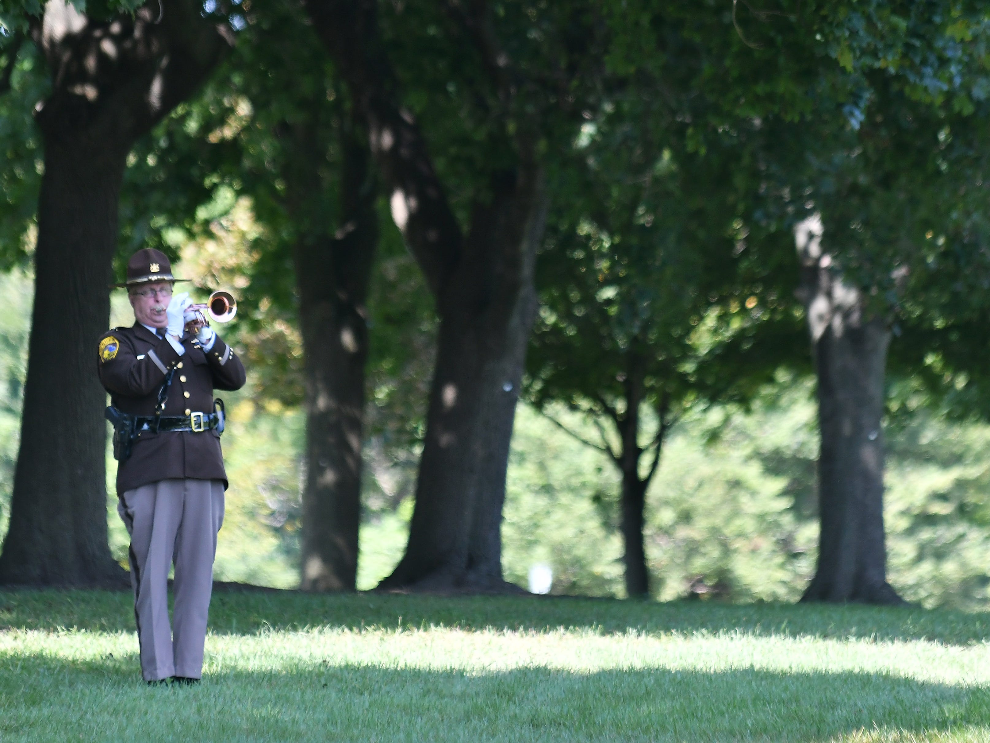 Oakland County Sheriff Deputy James Gregory plays taps during the ceremony.