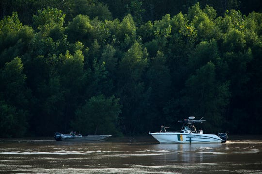 "Conservation officers with the Indiana Department of Natural Resources search the Ohio River near the Newburgh Dam for a missing fisherman, Steven O. Burks, 45, of Owensboro, Ky., Monday evening. Burks is missing after his fishing boat submerged at the dam as he and a friend, Paul W. Warrenfeltz, 48, also of Owensboro, were catching bait fish Sunday afternoon. Warrenfeltz was able to reach the dam safely. A sign on the dam reads ""Restricted – Keep back 150 feet."""