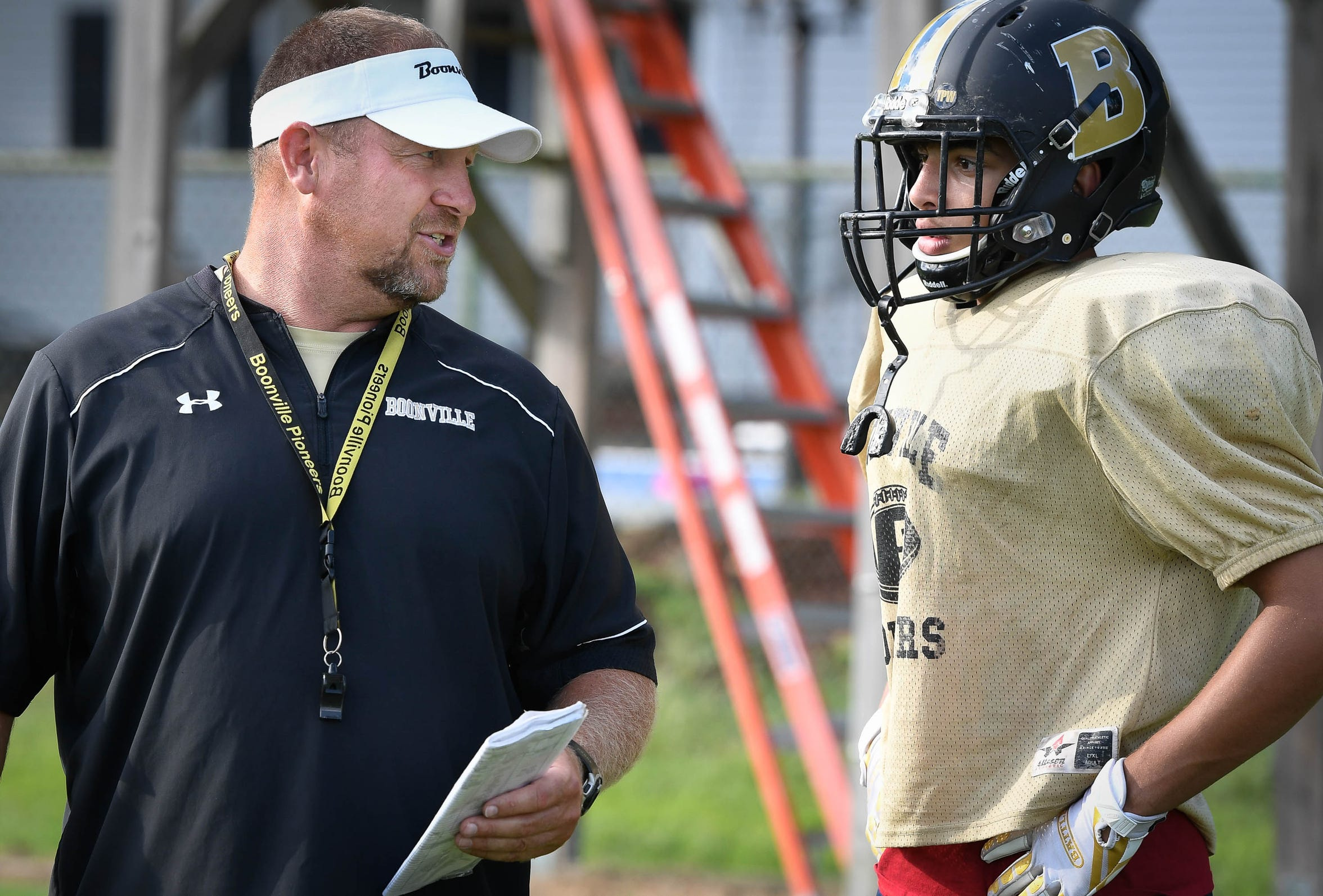 Boonville High top assistant coach Ben Wolfe talks with Devin Mockobee (5) during afternoon practice in Boonville Monday, September 10, 2018.