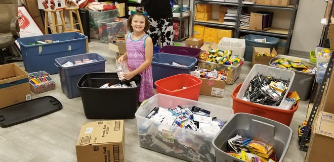 A young helper unpacks school items donated to the Salvation Army.