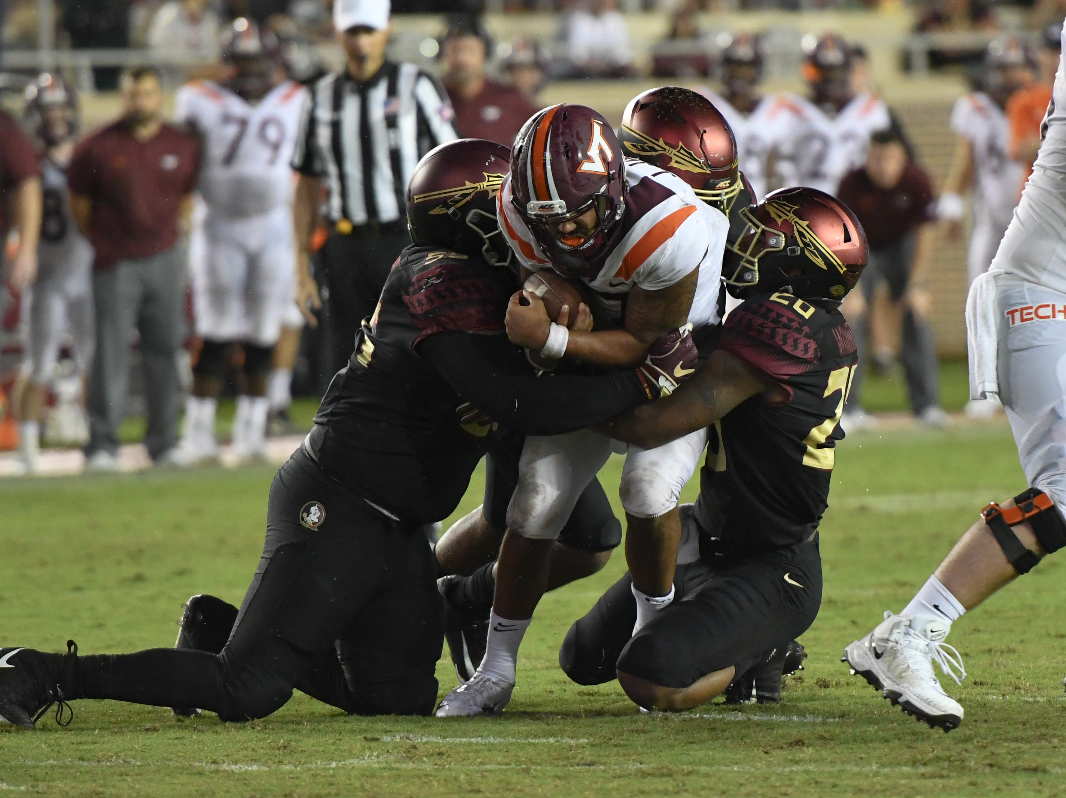 A couple of FSU defenders sacking Virginia Tech's quarterback during the third quarter of FSU's game against Virginia Tech on Monday night.