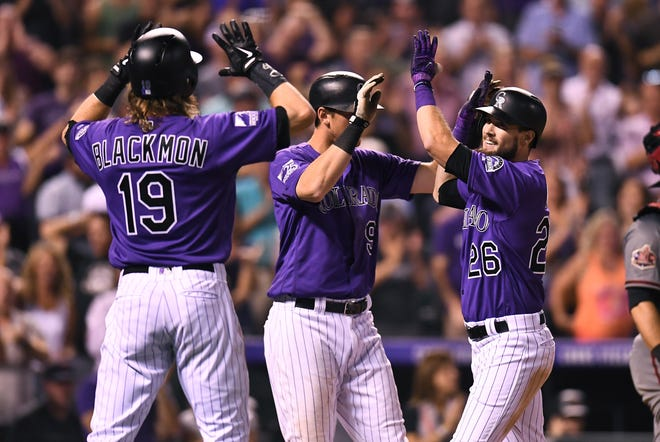 Colorado Rockies outfielder David Dahl, center, celebrates his first career grand slam during Monday night's win over the Arizona Diamondbacks with teammates Charlie Blackmon and D.J. LeMahieu. The Rockies and Diamondbacks continue a key four-game series Wednesday night with a 6:40 p.m. game at Coors Field in Denver.