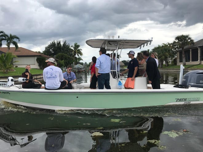 Ron DeSantis, in blue shirt and campaigning for governor of Florida, tours algae blooms in Cape Coral canals on Tuesday.