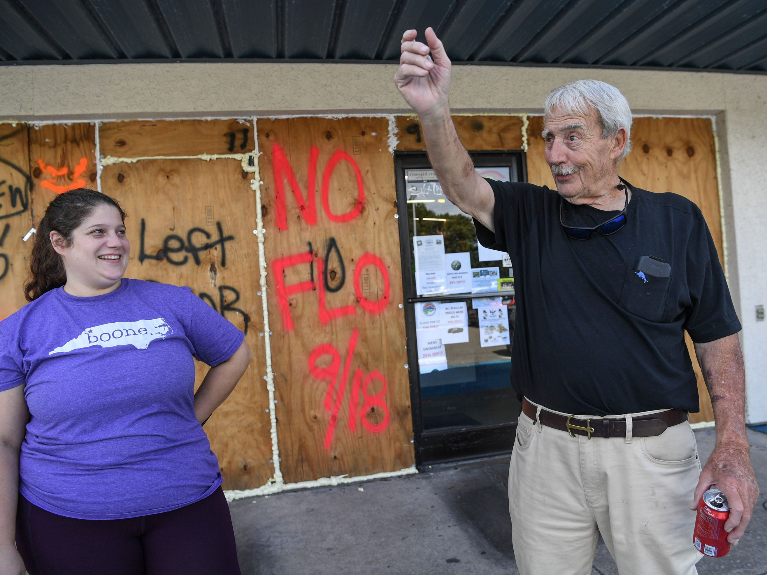 Meredith Reddick, left, and her father Gordon Reddick, owner of Redix store, talks about debris flying through the air and the need for plywood boards cover his windows, on Tuesday, September 11, 2018. Reddick has used the same boards since 1993, and wrote names for each storm since then. Hurricane Florence is expected to arrive in Wilmington, North Carolina late Thursday night through Friday morning. (Ken Ruinard / Greenville News / Gannett USA Today Network / 2018 )