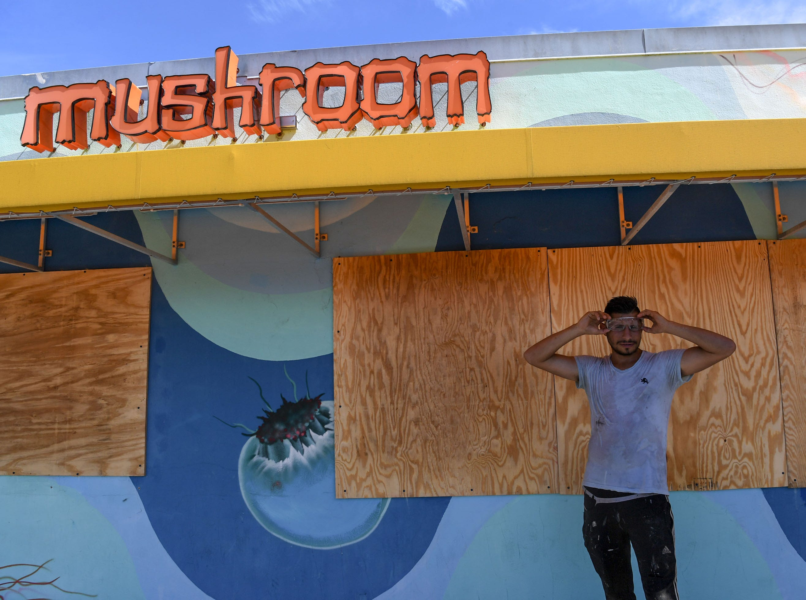 Ricardo Olivares, of Wilmington, North Carolina, covers windows at the Mellow Mushroom in Wilmington, North Carolina on Tuesday, September 11, 2018. Olivares said he is evacuating before Hurricane Florence arrives in Wilmington, North Carolina late Thursday night through Friday morning. (Ken Ruinard / Greenville News / Gannett USA Today Network / 2018 )
