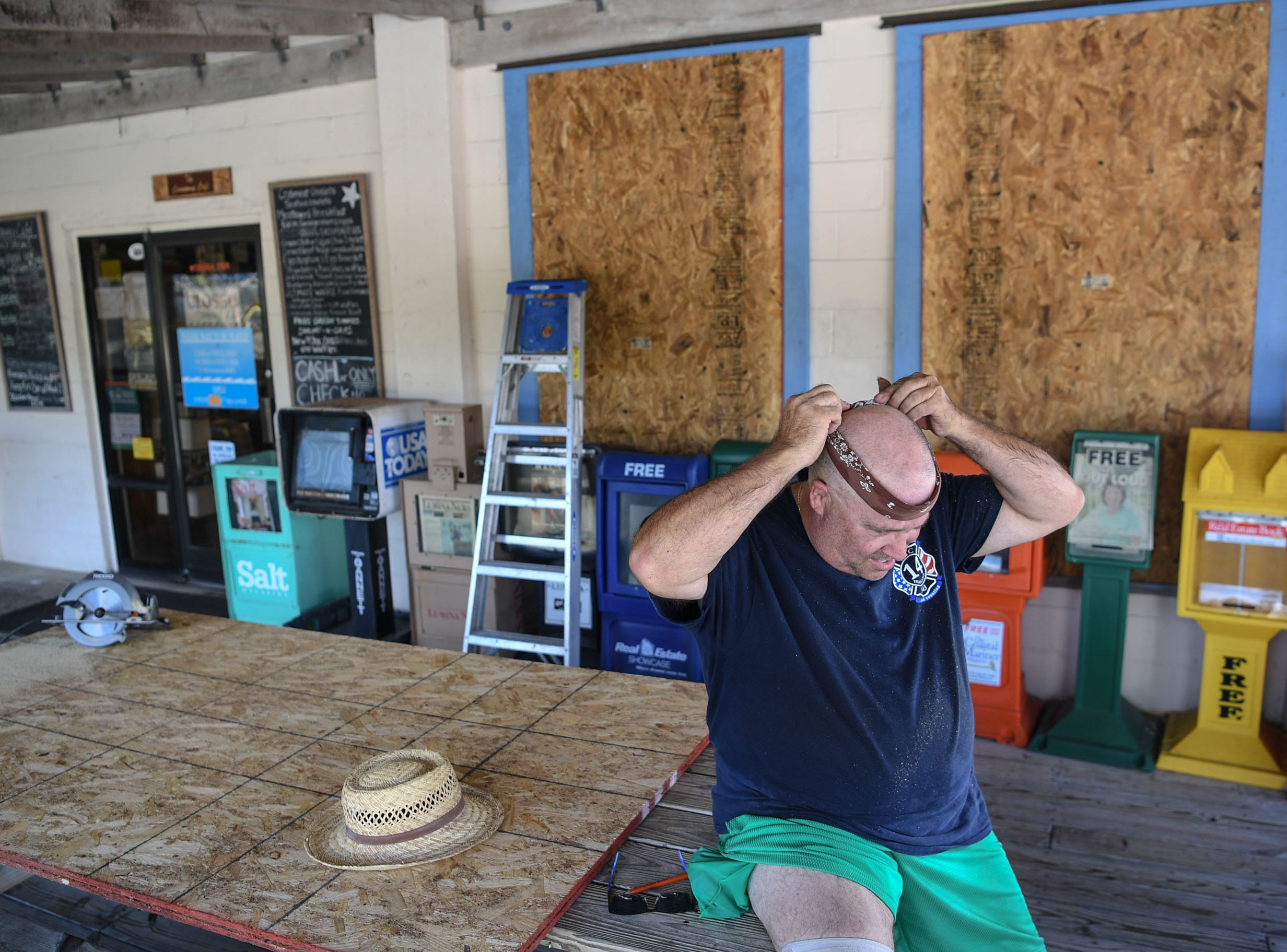 Jon Wright, 63, of Wilmington, North Carolina, puts a bandana on his head before wearing his hat and drilling screws to cover windows with plywood at the Causeway Cafe in Wilmington, North Carolina on Tuesday, September 11, 2018. Hurricane Florence is expected to arrive in Wilmington, North Carolina late Thursday night through Friday morning. (Ken Ruinard / Greenville News / Gannett USA Today Network / 2018 )