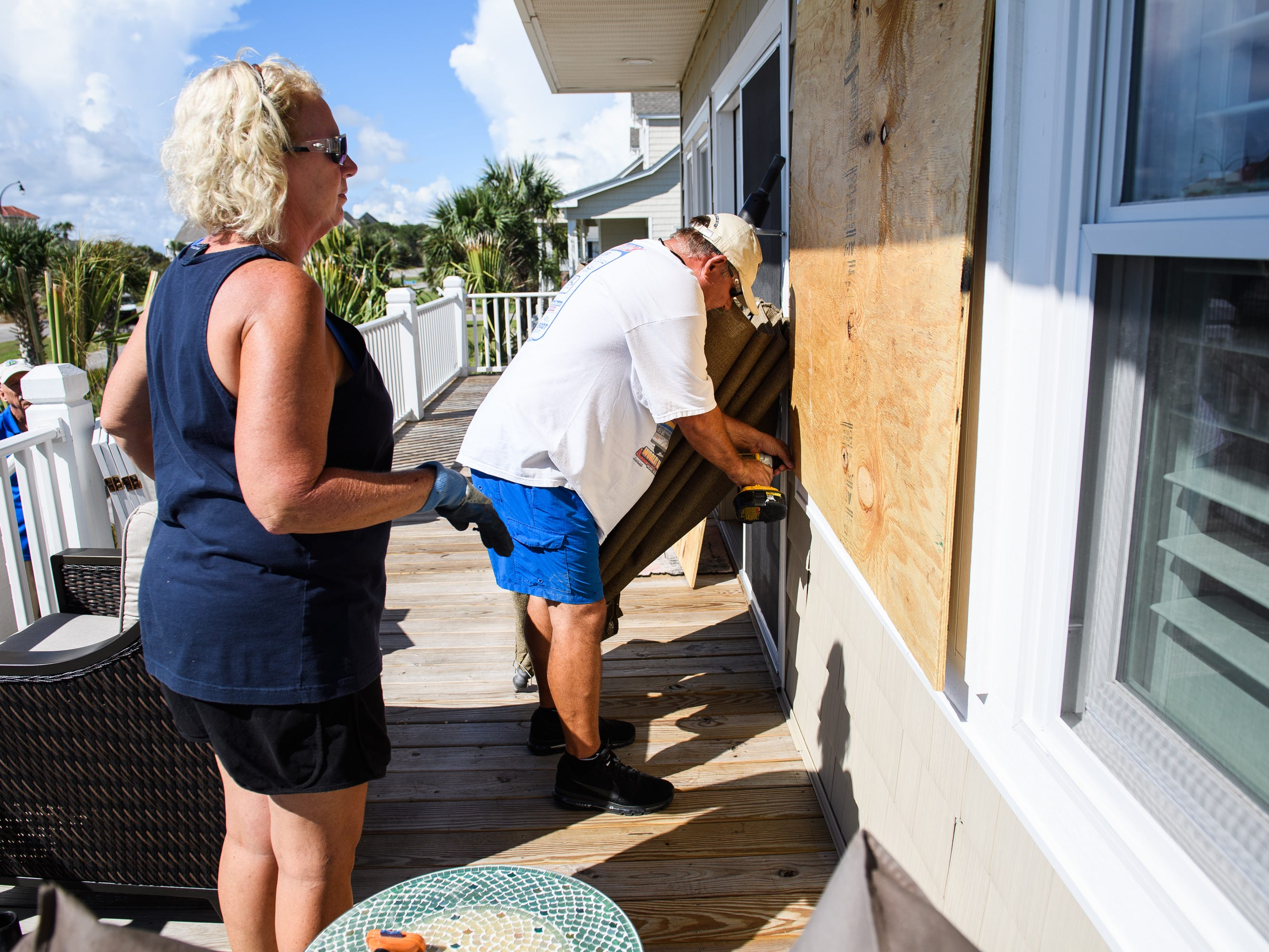 Angie Travis and her husband Jeff place large piece of plywood over a window on their vacation home as they prepare for Hurricane Florence on Tuesday, Sept. 11, 2018.