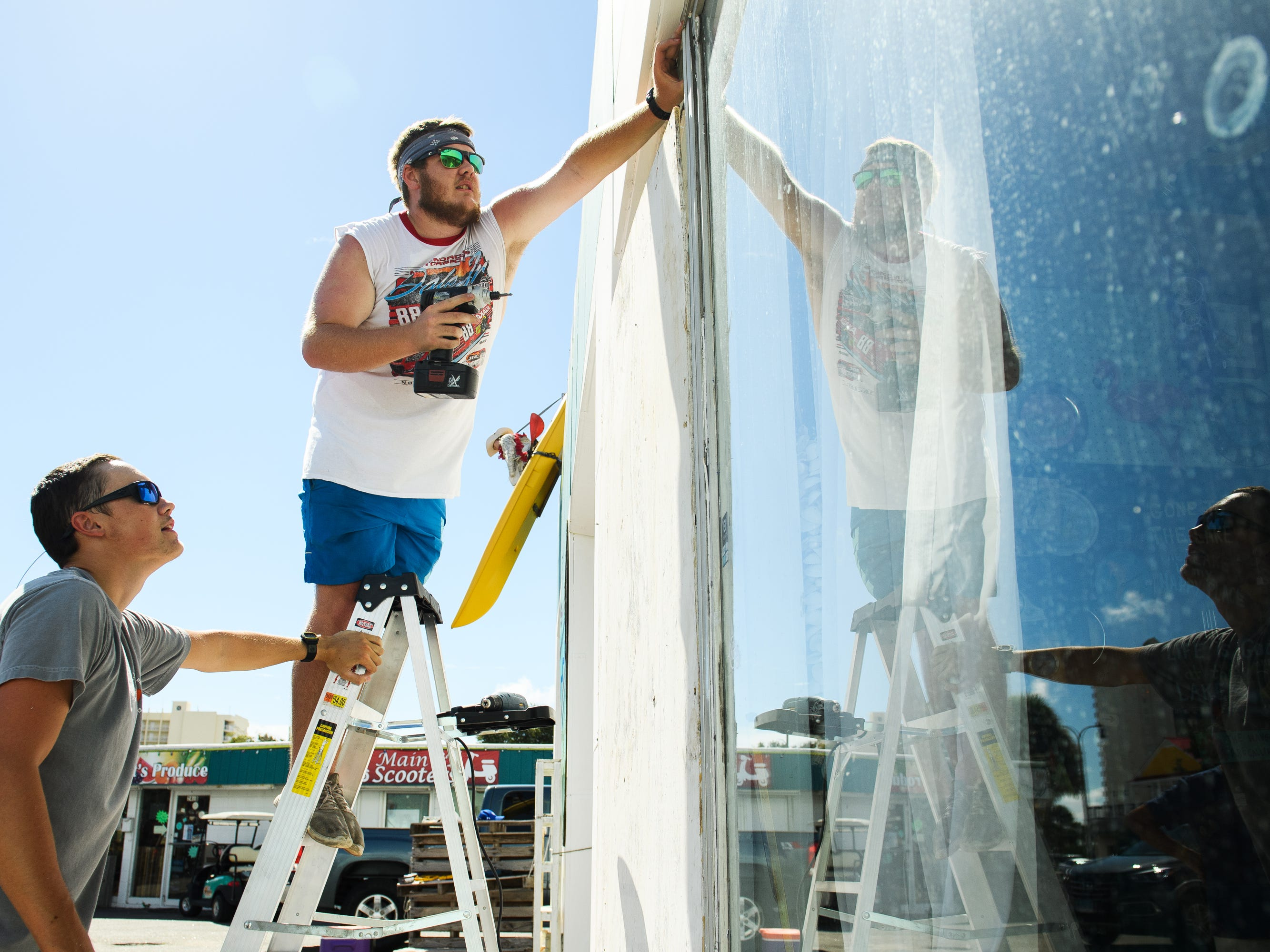 Hunter Cook and Austin Benton board up windows at their grandfather's business, The Wildflower, in North Myrtle Beach on Tuesday, Sept. 11, 2018.