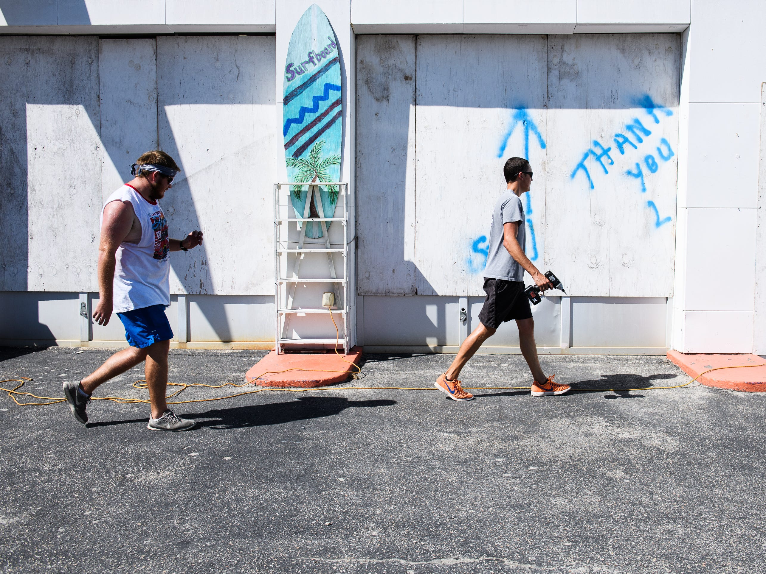 Hunter Cook and Austin Benton help their grandfather Tracy Berry board up his business, The Wildflower, in North Myrtle Beach on Tuesday, Sept. 11, 2018.