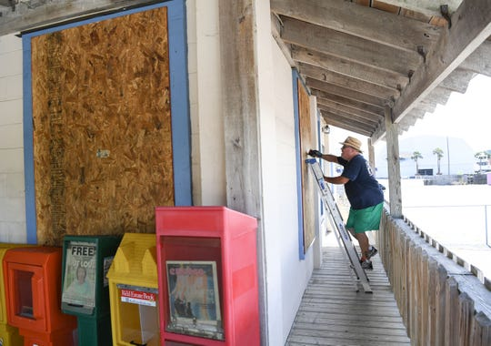Jon Wright, 63, of Wilmington, North Carolina, drills screws in plywood to cover windows at the Causeway Cafe in Wilmington, North Carolina on Tuesday, September 11, 2018. Hurricane Florence is expected to arrive in Wilmington, North Carolina late Thursday night through Friday morning. (Ken Ruinard / Greenville News / Gannett USA Today Network / 2018 )