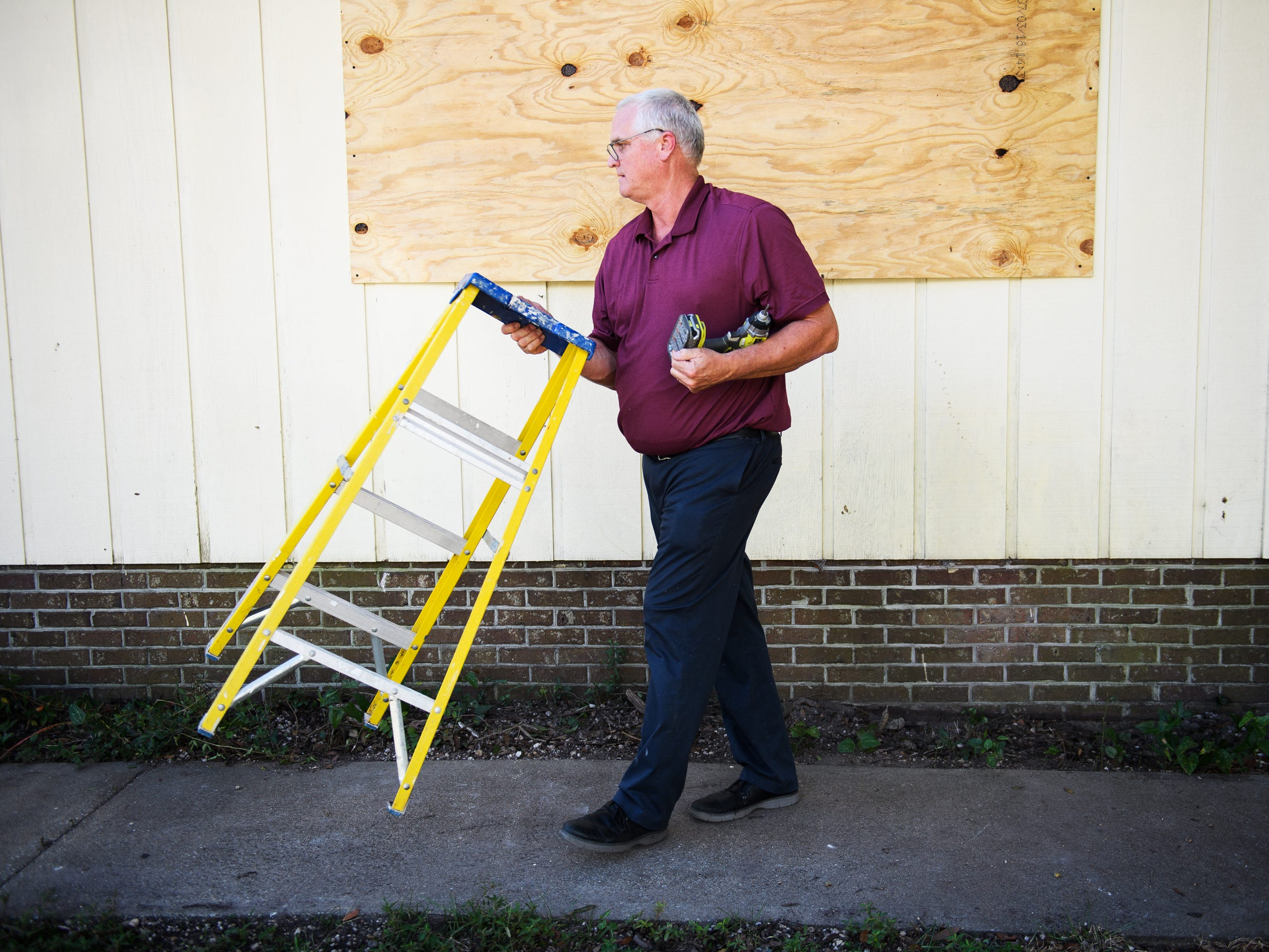 Don Ludemann boards up the windows of his second home in North Myrtle Beach on Tuesday, Sept. 11, 2018, days before Hurricane Florence is expected to hit the South and North Carolina coasts.