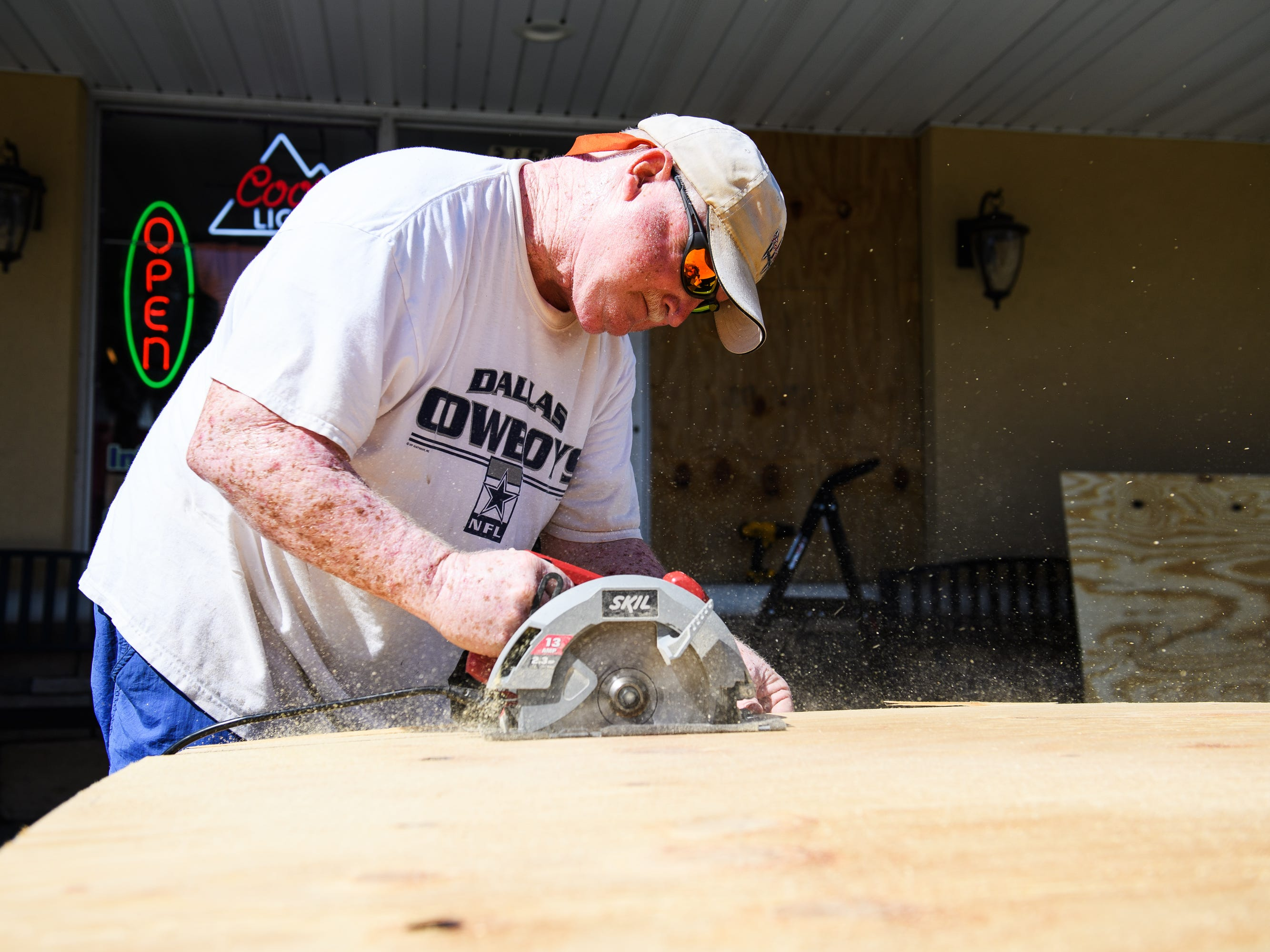 Lee Dorton, owner of Infused Olive in North Myrtle Beach, cuts pieces of plywood before placing them over the windows of his business on Tuesday, Sept. 11, 2018.