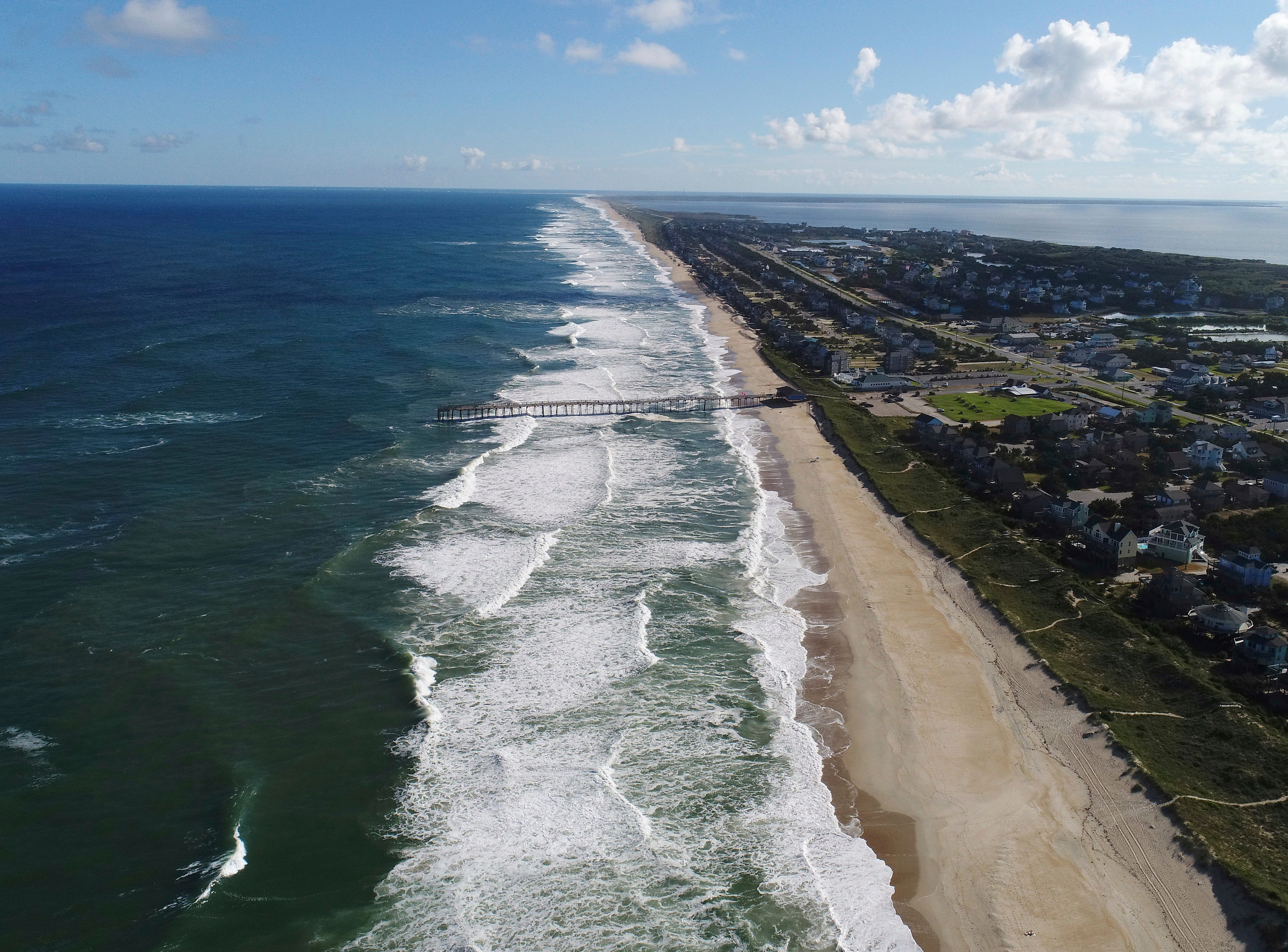 "In this Monday afternoon, Sept. 10, 2018 photo provided by DroneBase, waves crash along Avon, N.C., in the Outer Banks ahead of Hurricane Florence. Florence churned Tuesday, Sept. 11, toward the Eastern Seaboard as a storm of ""staggering"" size, forcing a million people to evacuate the coast."