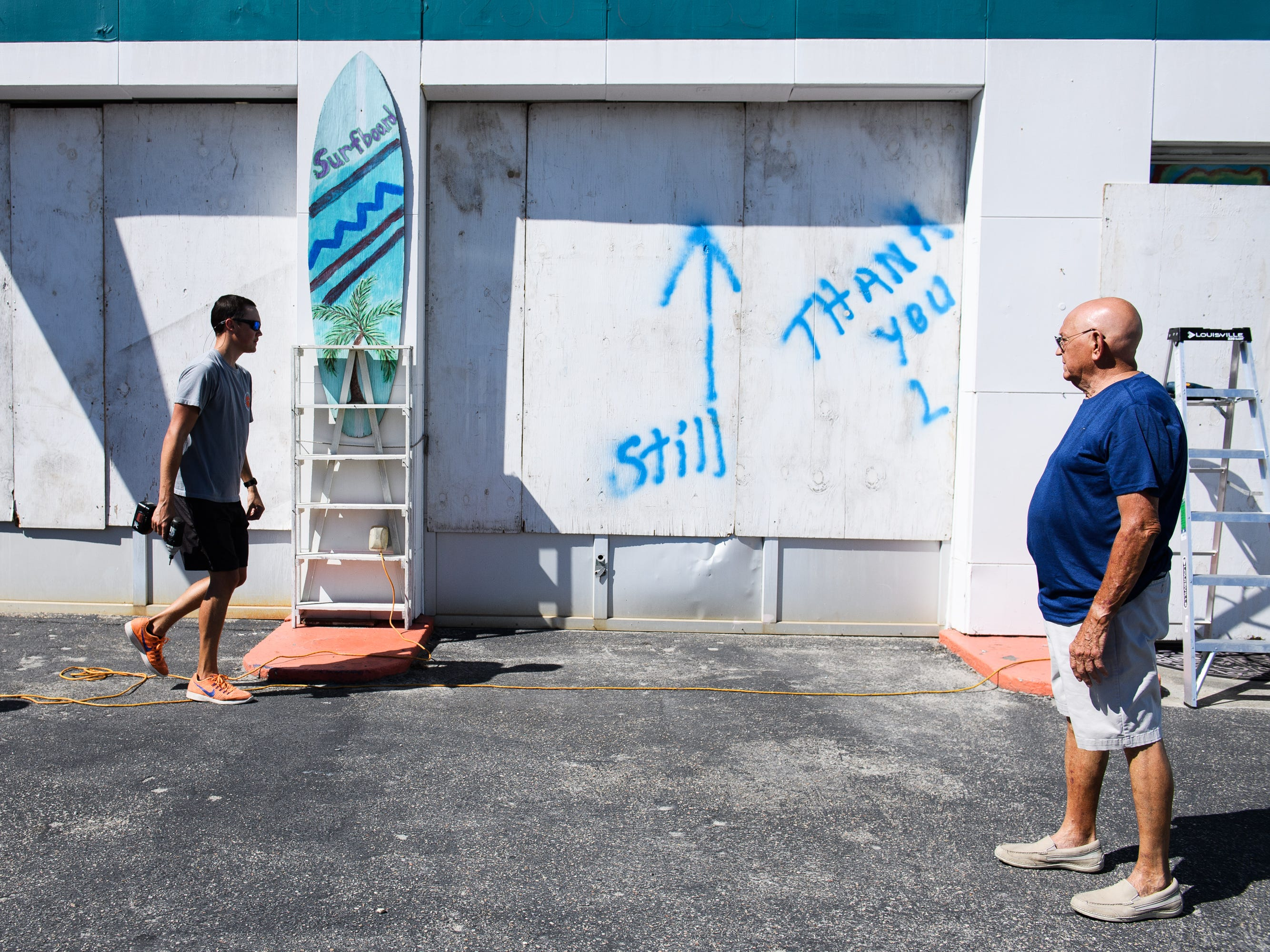 Austin Benton helps his grandfather Tracy Berry board up his business, The Wildflower, in North Myrtle Beach on Tuesday, Sept. 11, 2018.