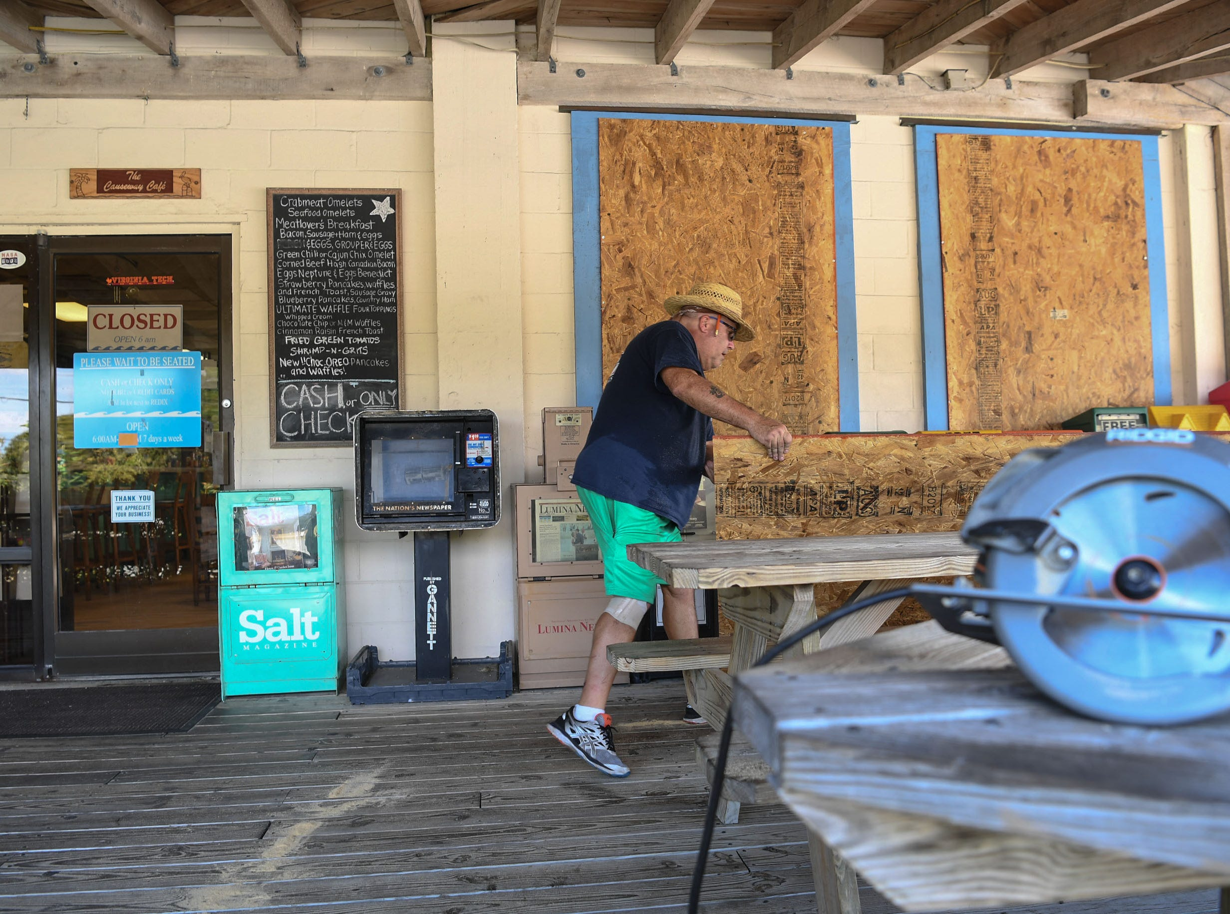 Jon Wright, 63, of Wilmington, North Carolina, covers windows at the Causeway Cafe in Wilmington, North Carolina on Tuesday, September 11, 2018. Hurricane Florence is expected to arrive in Wilmington, North Carolina late Thursday night through Friday morning. (Ken Ruinard / Greenville News / Gannett USA Today Network / 2018 )