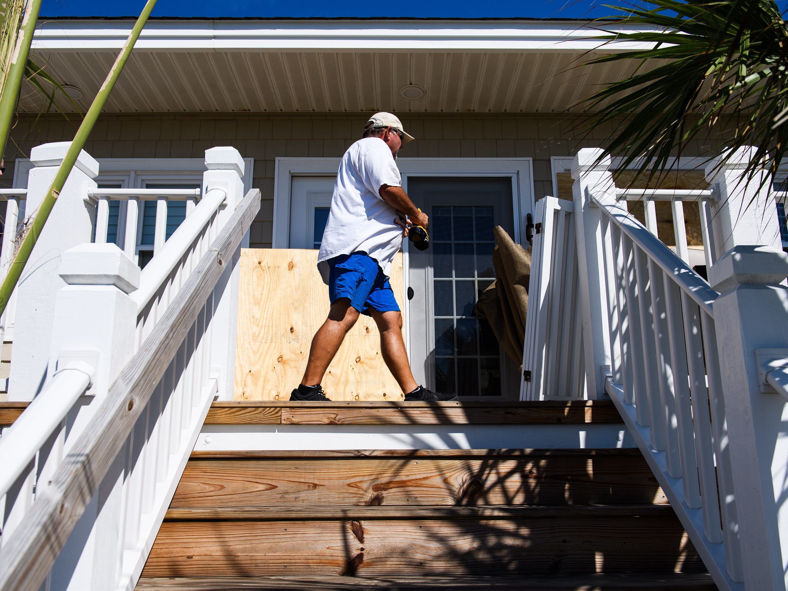 Jeff Travis works to board up windows on his vacation home as and his wife Angie prepare for Hurricane Florence on Tuesday, Sept. 11, 2018.