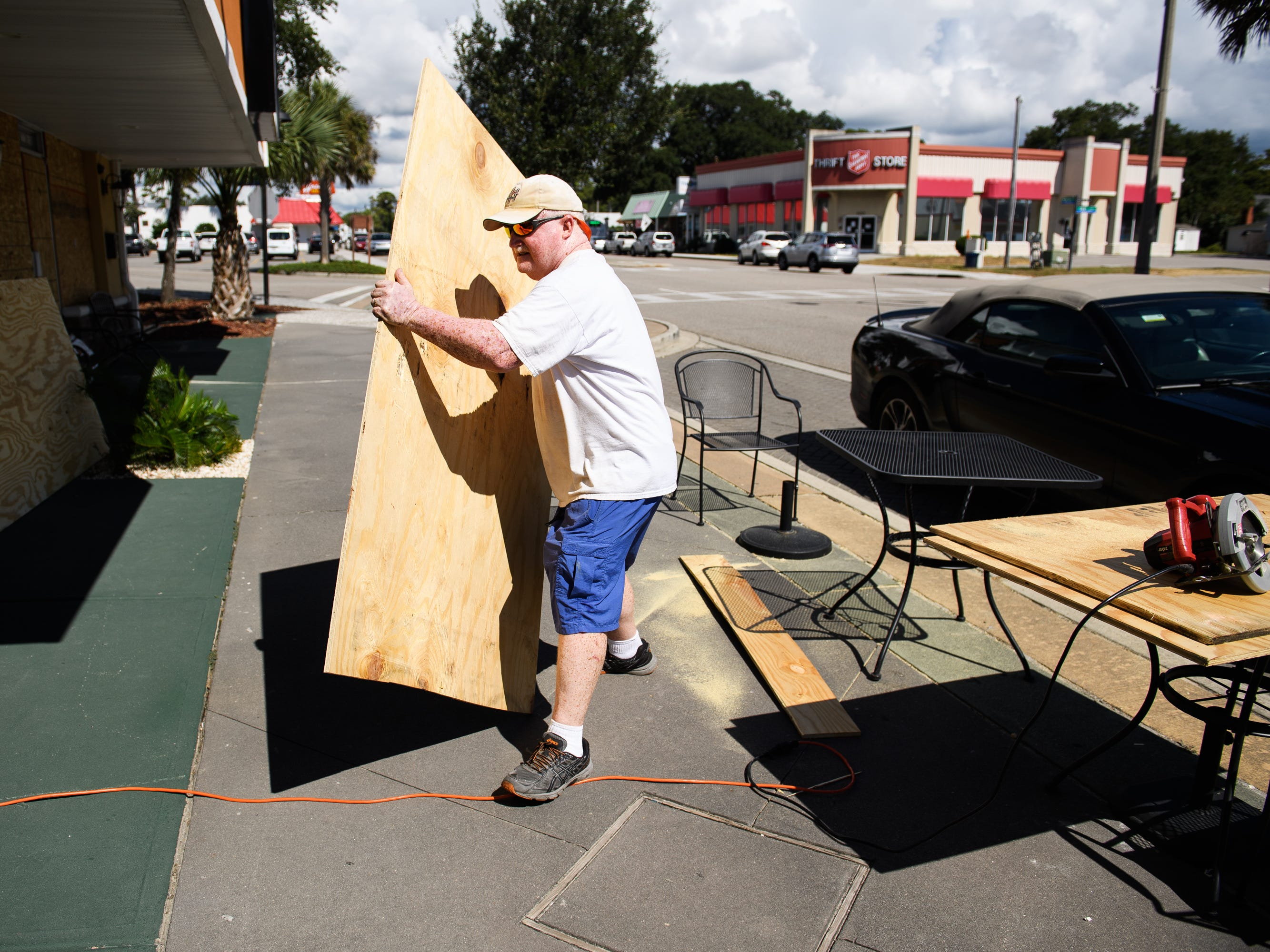 Lee Dorton, owner of Infused Olive in North Myrtle Beach, carries a large piece of plywood over to his business on Tuesday, Sept. 11, 2018.