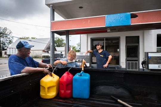A man who identified himself as Little Ron, has his gas jugs filled up at Ryan's Garage in Swan Quarter with Tony Brooks, and Ryan Marshall as he prepares for Hurricane Florence Sept. 11, 2018.
