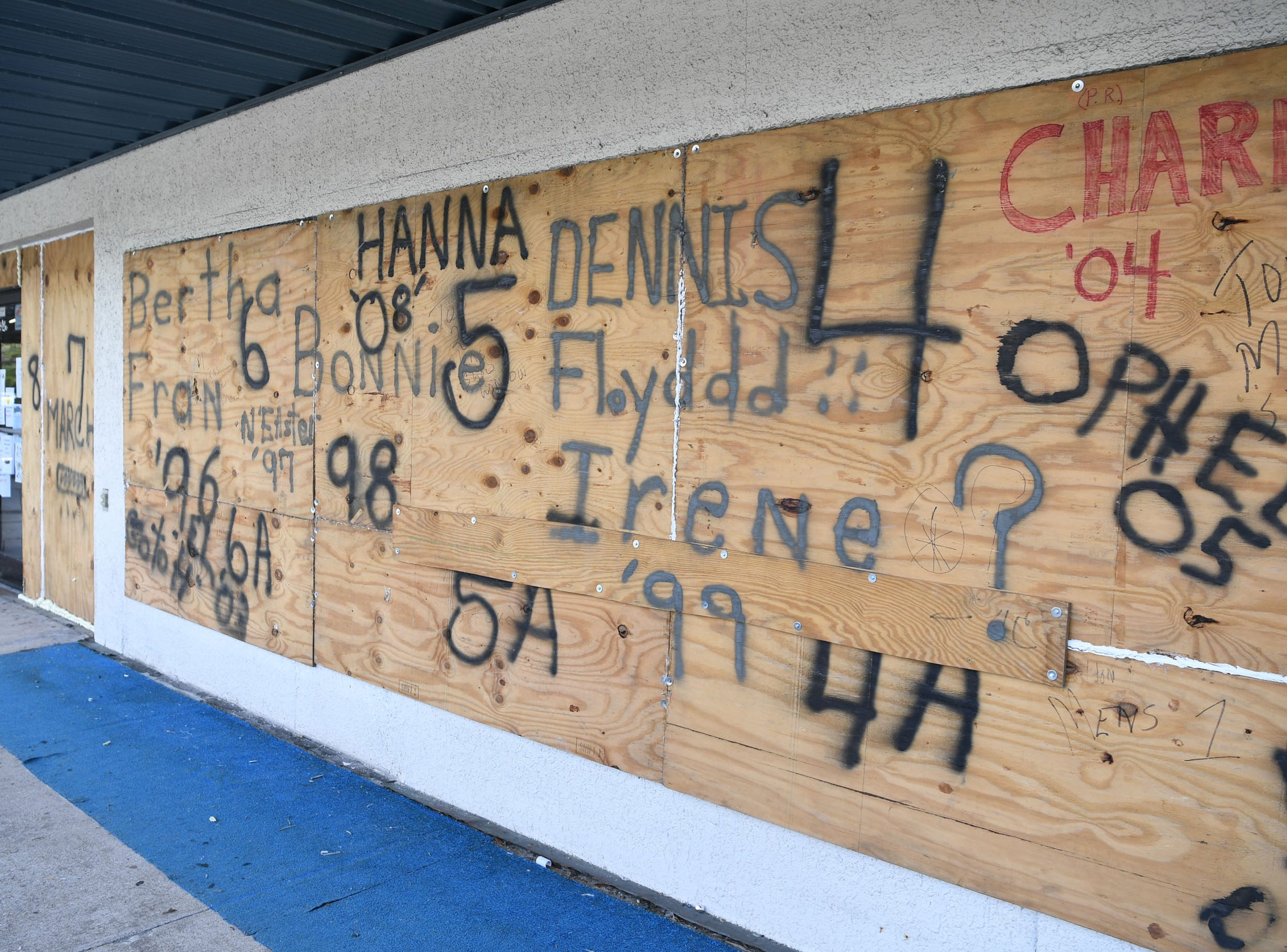 Plywood boards cover windows at Redix store at Wrightsville Beach on Tuesday, September 11, 2018. Gordon Reddick, owner of the store has used the same boards since 1993, and wrote names for each storm since then. Hurricane Florence is expected to arrive in Wilmington, North Carolina late Thursday night through Friday morning. (Ken Ruinard / Greenville News / Gannett USA Today Network / 2018 )