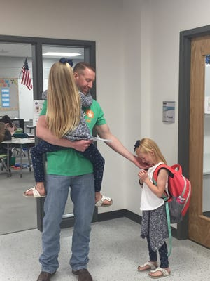 Seth Swaboski, a member of the Air Force, holds daughter Aleigh and reaches out to daughter Lexi Tuesday at Giant Springs Elementary. Swaboski surprised his daughters at school after returning from a deployment in Afghanistan.