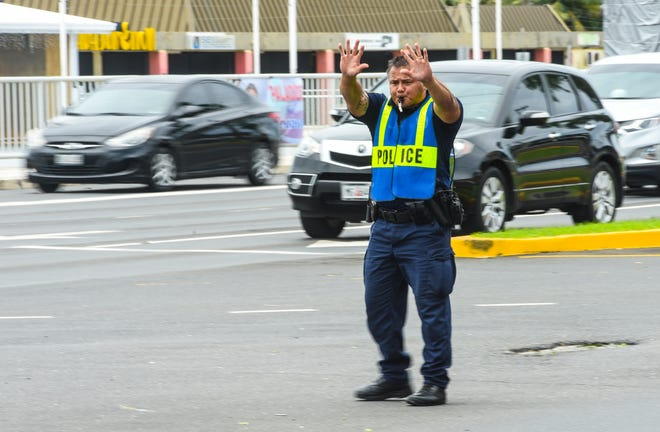 Guam Police Department Officer S.G. Topasna directs traffic as motorists converge at the intersection of Route 8 and Marine Corps Drive in Hagåtña on Tuesday, Sept. 11, 2018. The traffic control light at the intersection was inoperable at the time due the passage of Typhoon Mangkhut the evening before.