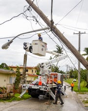 Guam Power Authority linemen prepare to remove a broken wooden power pole, suspended above Torres Street in Yigo only by the lines connected to it, in the aftermath of Typhoon Mangkhut on Tuesday, Sept. 11, 2018.