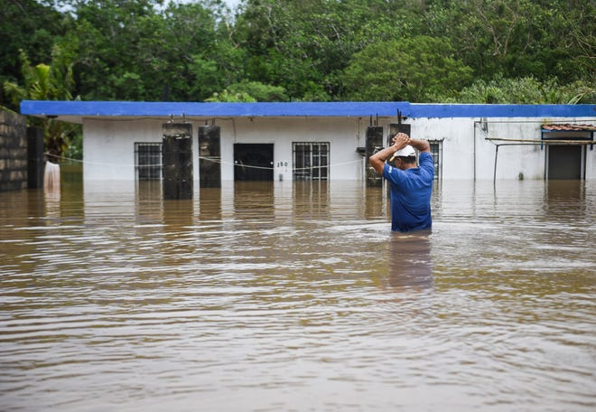 Yigo Mayor Rudy Matanane wades through waist-deep water to check on the flooded home of Ronald San Nicolas in the aftermath of Typhoon Mangkhut on Tuesday, Sept. 11, 2018.