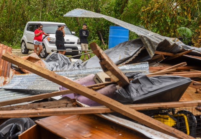 Dededo resident and mother of three, Redina Perez, wipes her eyes as she and other family members contemplate their limited options after finding her wood and tin home in ruins in the aftermath of Typhoon Mangkhut on Tuesday, Sept. 11, 2018.