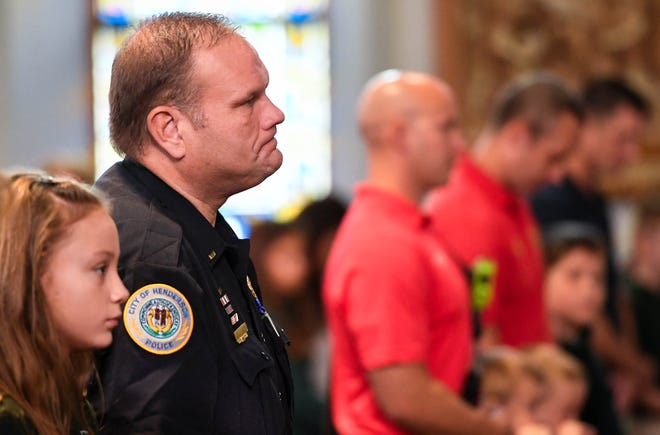 Acting Henderson Police Chief Jason Hargitt with his daughter Caeson, 10 years-old, attend the morning Mass for First Responders held at Henderson's Holy Name of Jesus Catholic Church Tuesday, September 11, 2018.