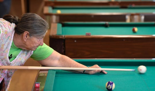 Lining up her shot, Sharon McMican plays pool in the Henderson Senior Games 9-Ball tournament held at the Gathering Place Tuesday, September 11, 2018.
