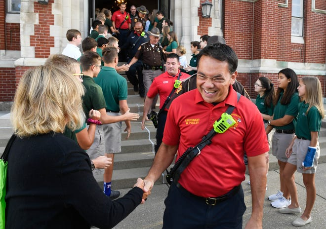 Henderson Fire Department Lt. Michael Polley runs a gauntlet of hand shakes from Holy Name students and faculty following the morning Mass for First Responders held at Henderson's Holy Name of Jesus Catholic Church Tuesday, September 11, 2018.