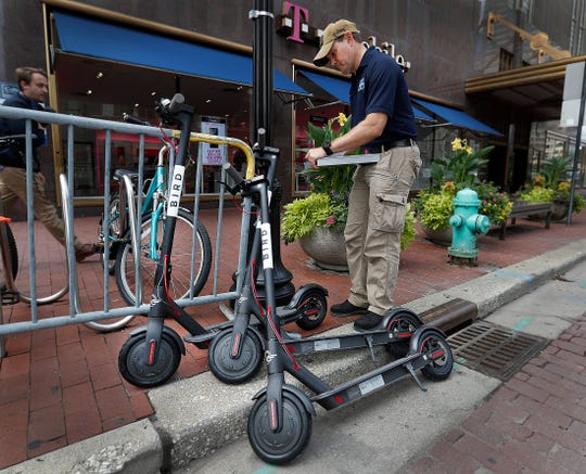 City inspector Matt Borden inspects scooters that were improperly parked. Inspectors from the Department of Business and Neighborhood Services (BNS) make their rounds inspecting scooters and making sure scooter riders are educated about the parking rules downtown Indianapolis on Sept. 11, 2018. Some of those rules include, leaving 4 feet of unobstructed passageway, parking the scooter in an upright manner, blocking entrances or exits to buildings, parking near a bike rack or docking station.