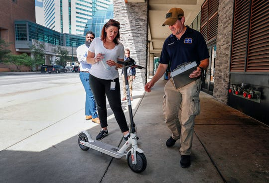 Inspectors from the Department of Business and Neighborhood Services (BNS) make their rounds inspecting scooters and making sure scooter riders are educated about the parking rules downtown Indianapolis on Sept. 11, 2018. Some of those rules include, leaving 4 feet of unobstructed passageway, parking the scooter in an upright manner, blocking entrances or exits to buildings, parking near a bike rack or docking station.