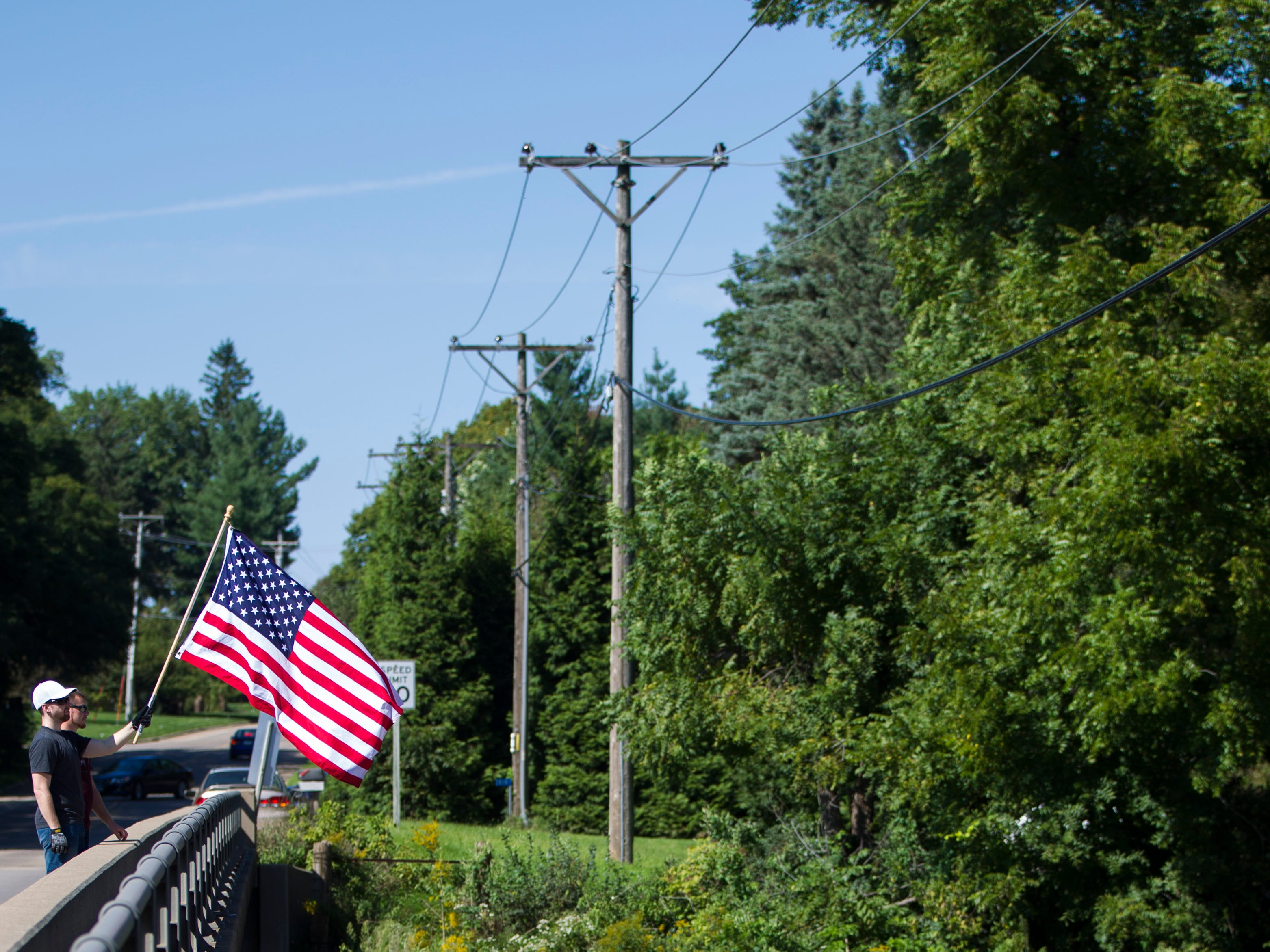 Two men wave an American flag on Tuesday, Sept. 11, 2018, on Prairie Du Chien Road over Interstate 80 in Iowa City while passersby honk their horns in support.