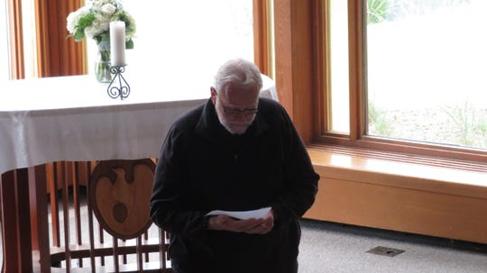 Rev. Carsten Martensen, a Catholic chaplain, reads a prayer at Ithaca College's Muller Chapel during a time of reflection and remembrance of 9/11.