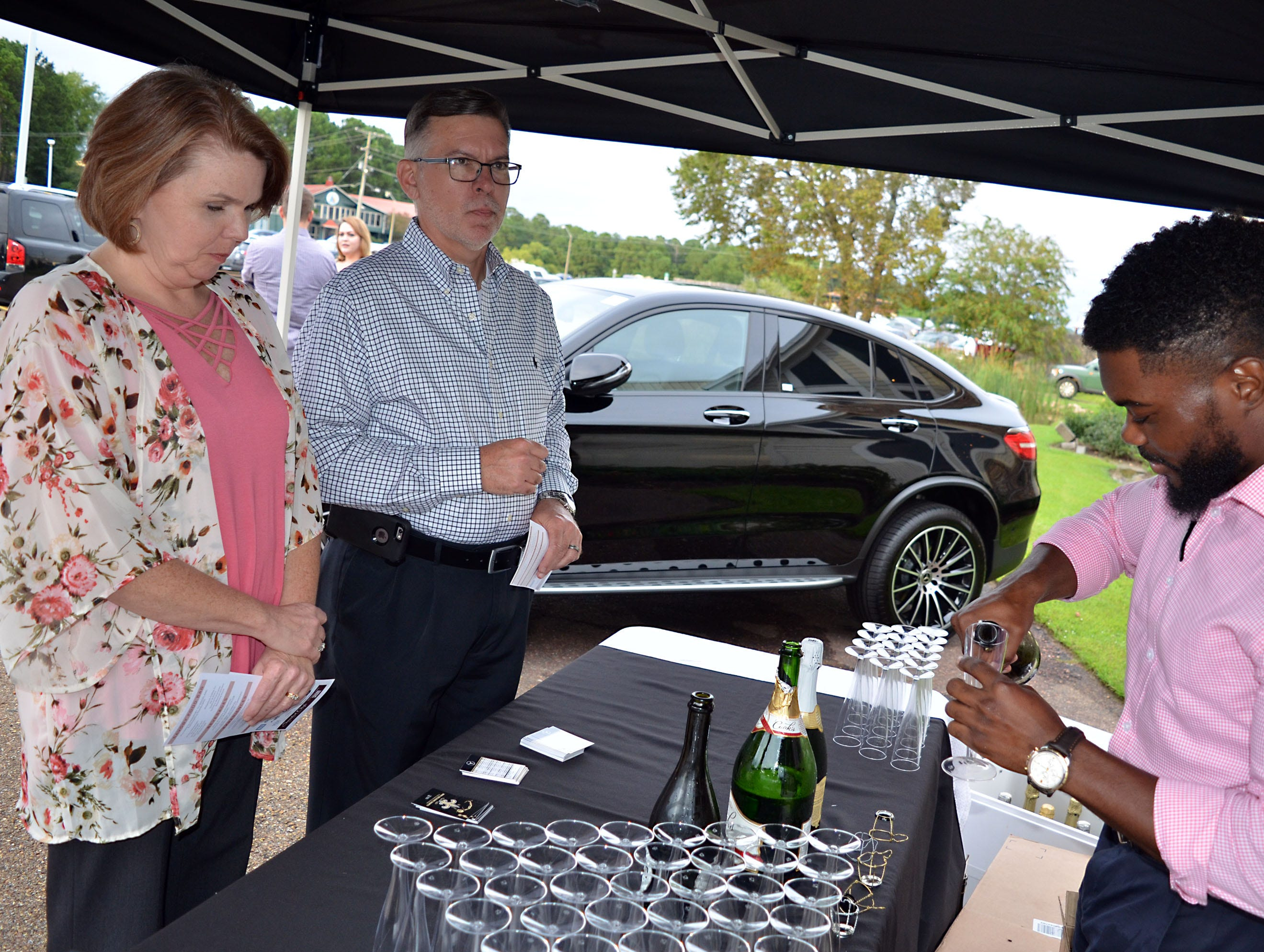 Andre Johnson, right, serves Angie and Vic Prather, of Mendenhall, a glass of champagne as they arrive at The Sweetest Chefs of the South event held Monday at The Lake House in Ridgeland.
