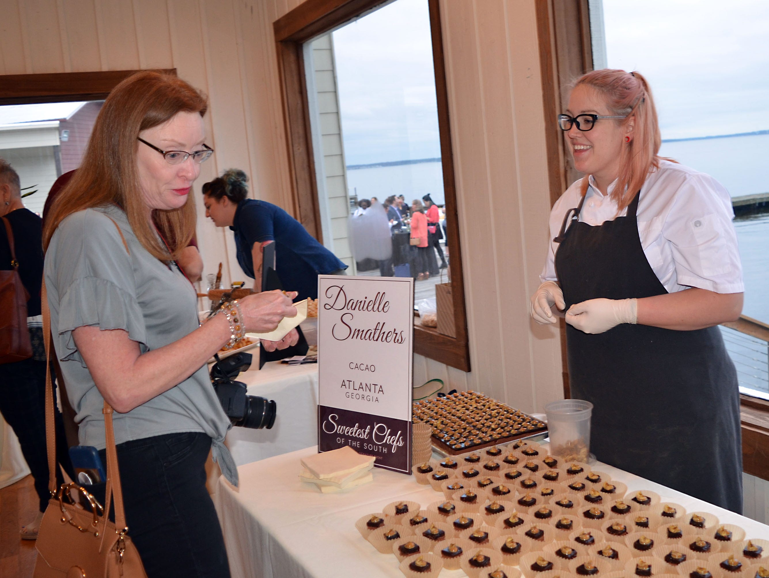 Kelly Mott, left, enjoys the delicious Banana Split Moose Cake prepared by one of the Sweetest Chefs, Danielle Smathers, with Cacoa of Atlanta.