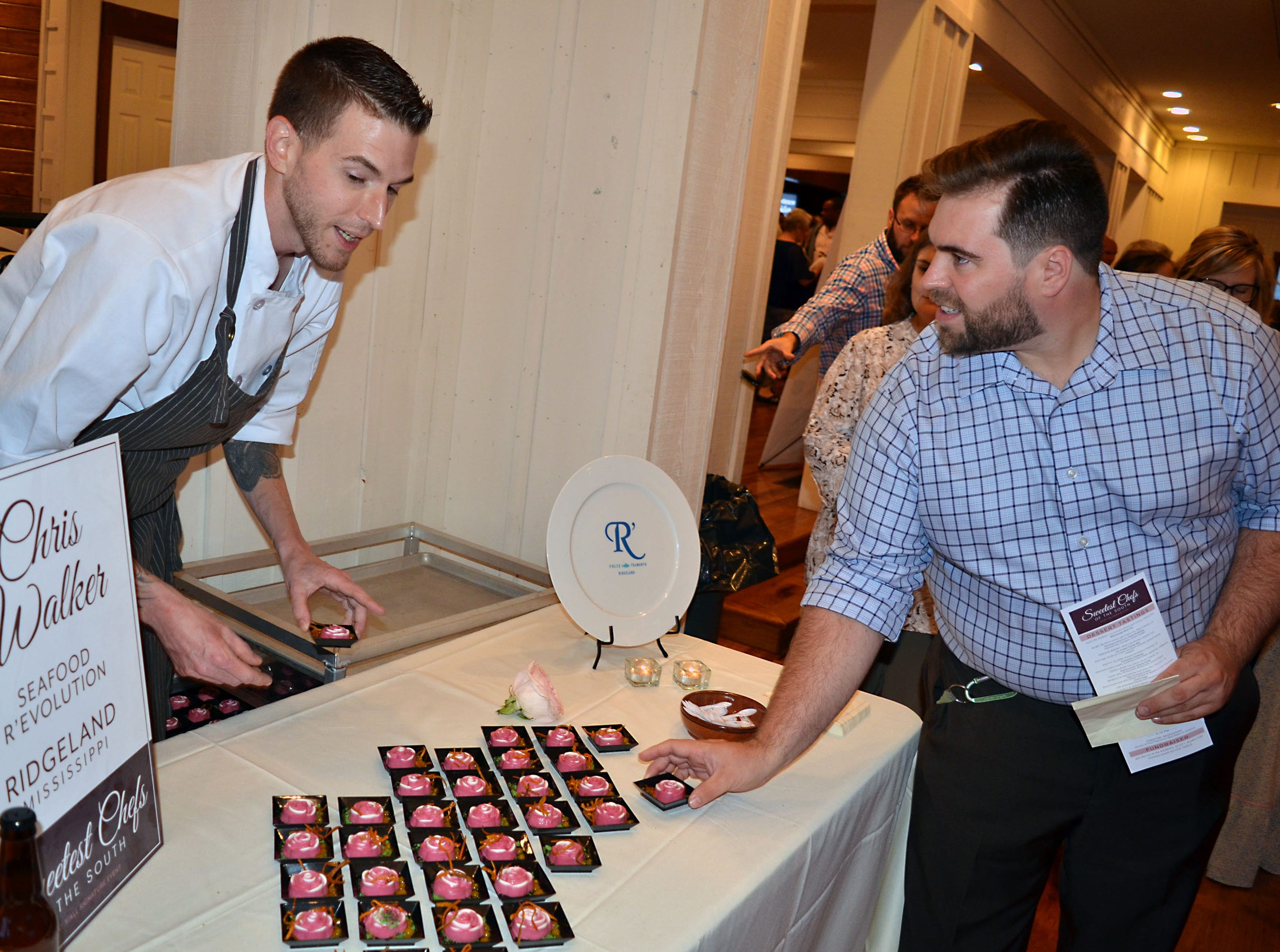 Dylan Brown, right, of Brandon, talks with Seafood Revolution pastry chef, Chris Walker about the hibiscus panna cotta he has prepared for The Sweetest Chefs event.