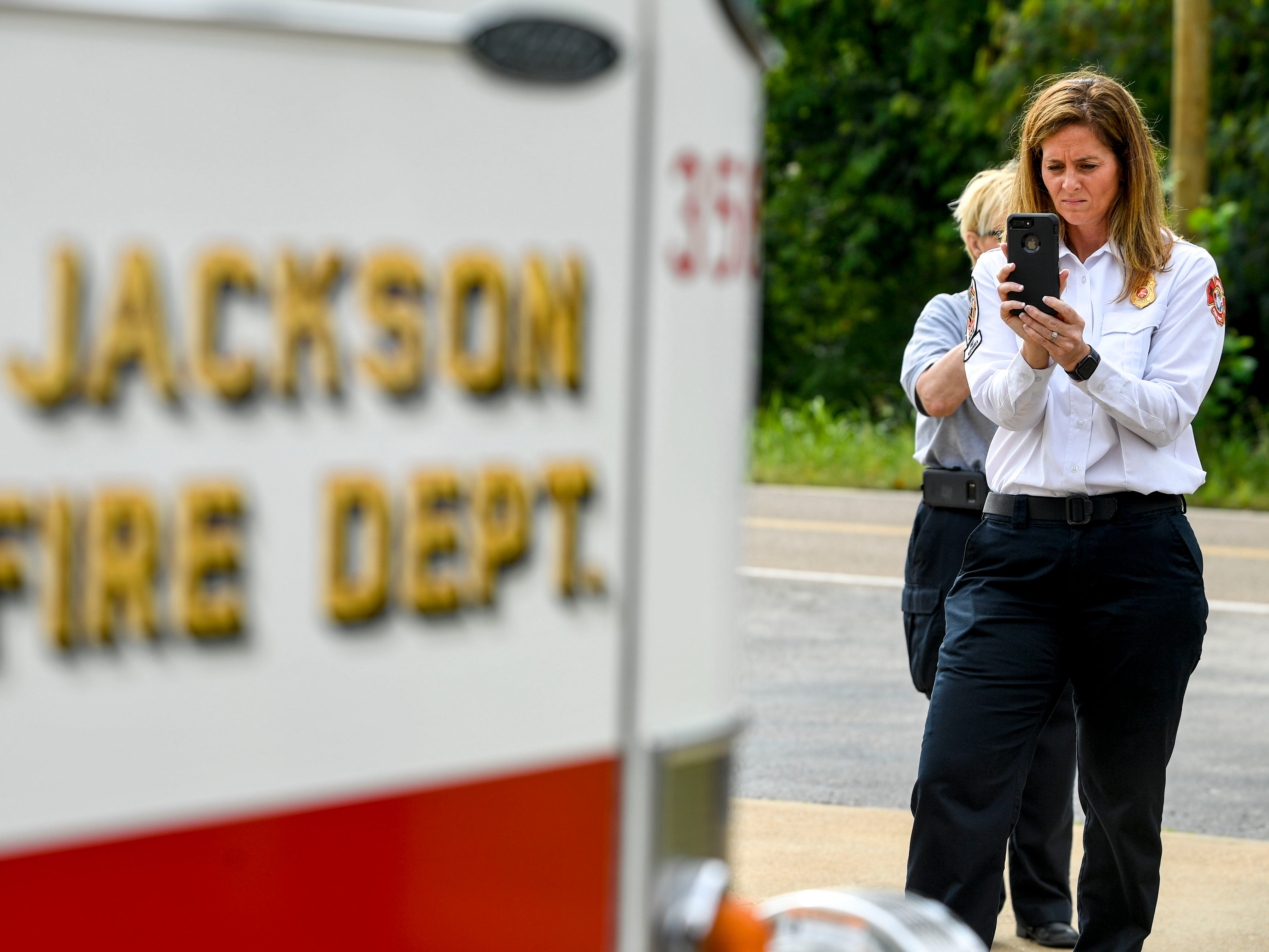 Jana Compton, a training officer with the Jackson Fire Department, takes photos of the procedures during a ceremony honoring the victims of the 9/11 attacks at Fire Station 3 in Jackson, Tenn., on Tuesday, Sept. 11, 2018.