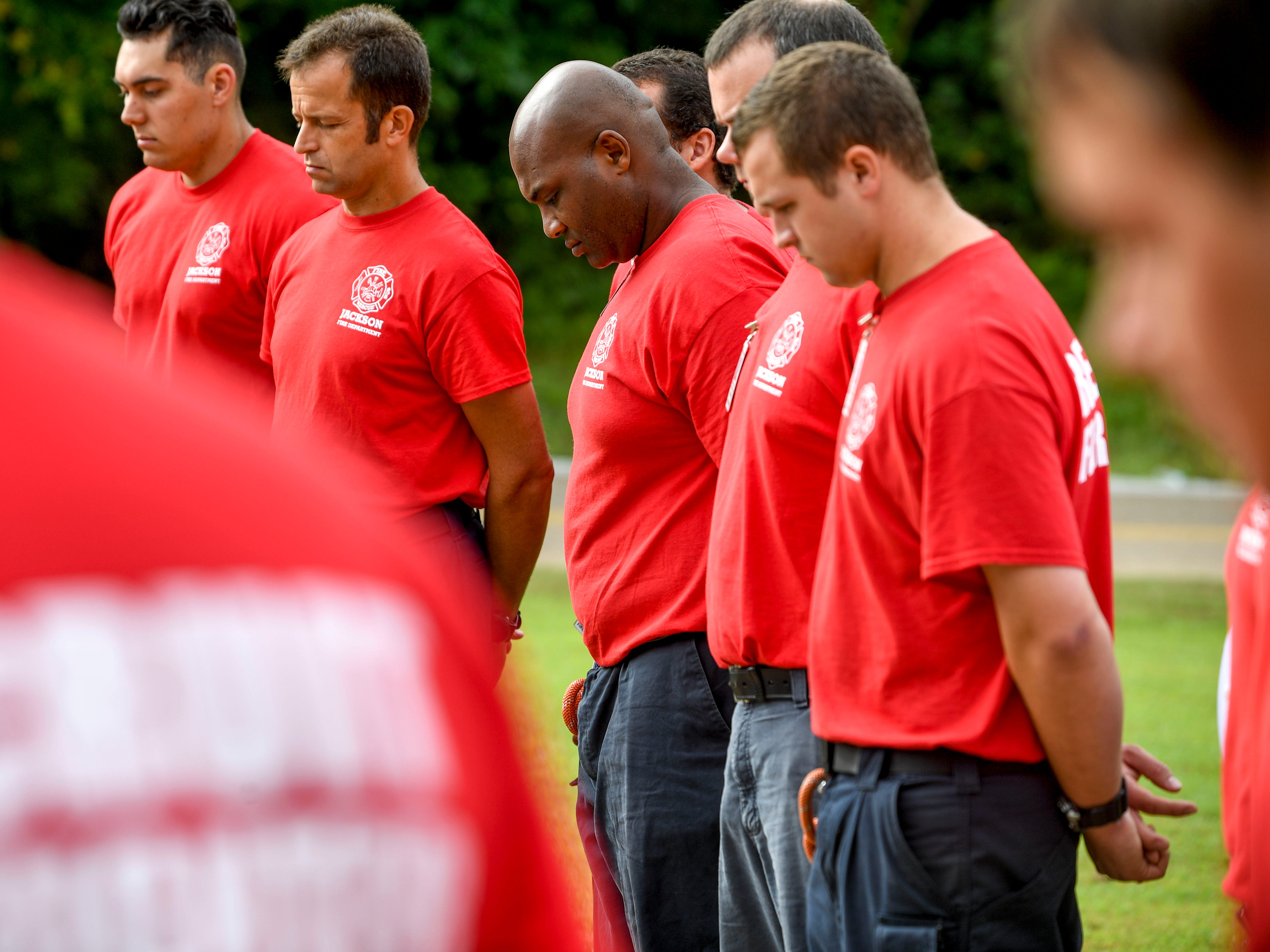 New firefighter recruits for the Jackson Fire Department bow their heads during a ceremony honoring the victims of the 9/11 attacks at Fire Station 3 in Jackson, Tenn., on Tuesday, Sept. 11, 2018.