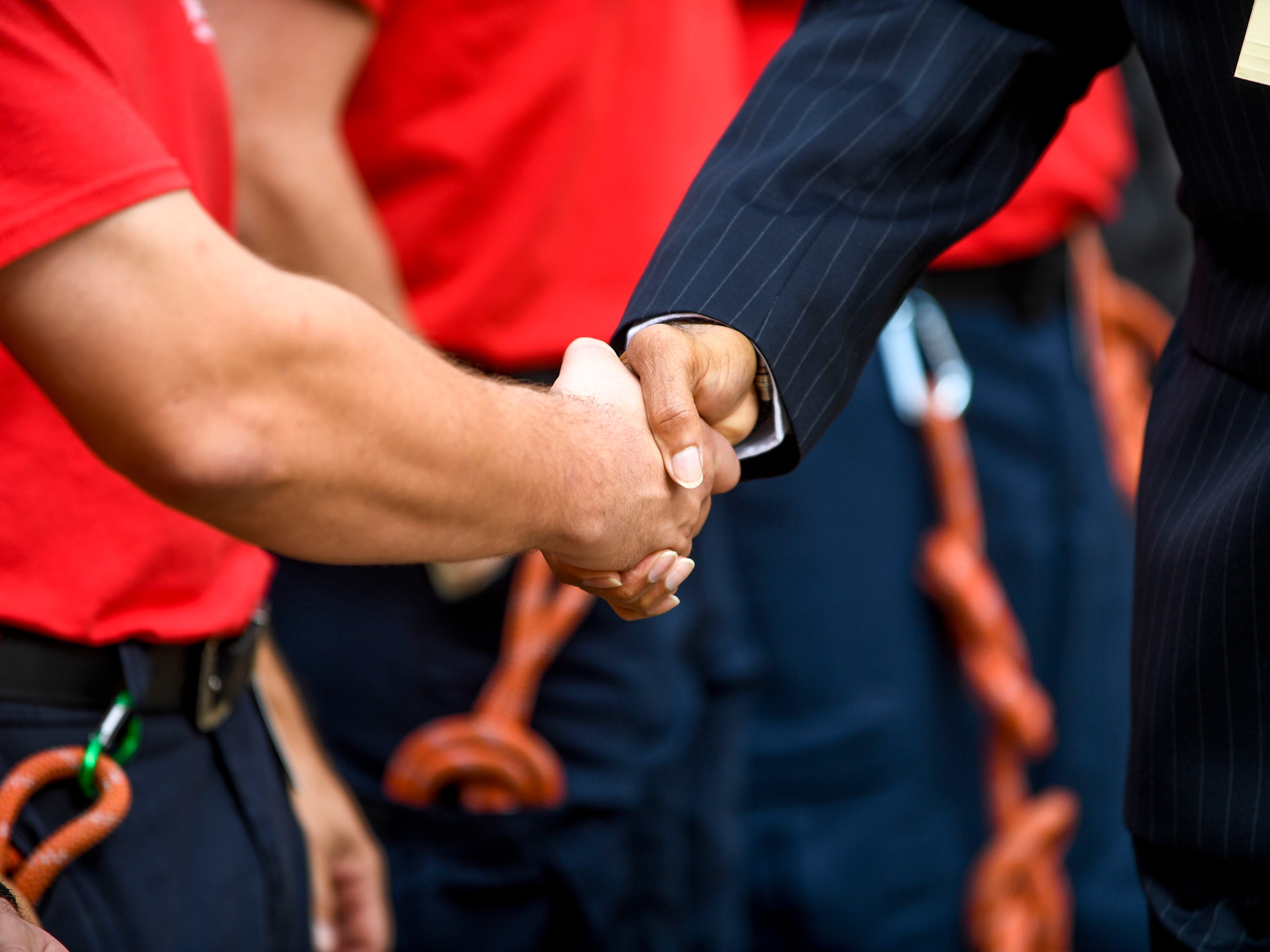 Fire chief Darryl Samuels shakes the hands of new fire department recruits after a ceremony honoring the victims of the 9/11 attacks at Fire Station 3 in Jackson, Tenn., on Tuesday, Sept. 11, 2018.