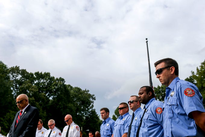 Jackson Firefighters bow their heads during a moment of silence during a ceremony honoring the victims of the 9/11 attacks at Fire Station 3 in Jackson, Tenn., on Tuesday, Sept. 11, 2018.