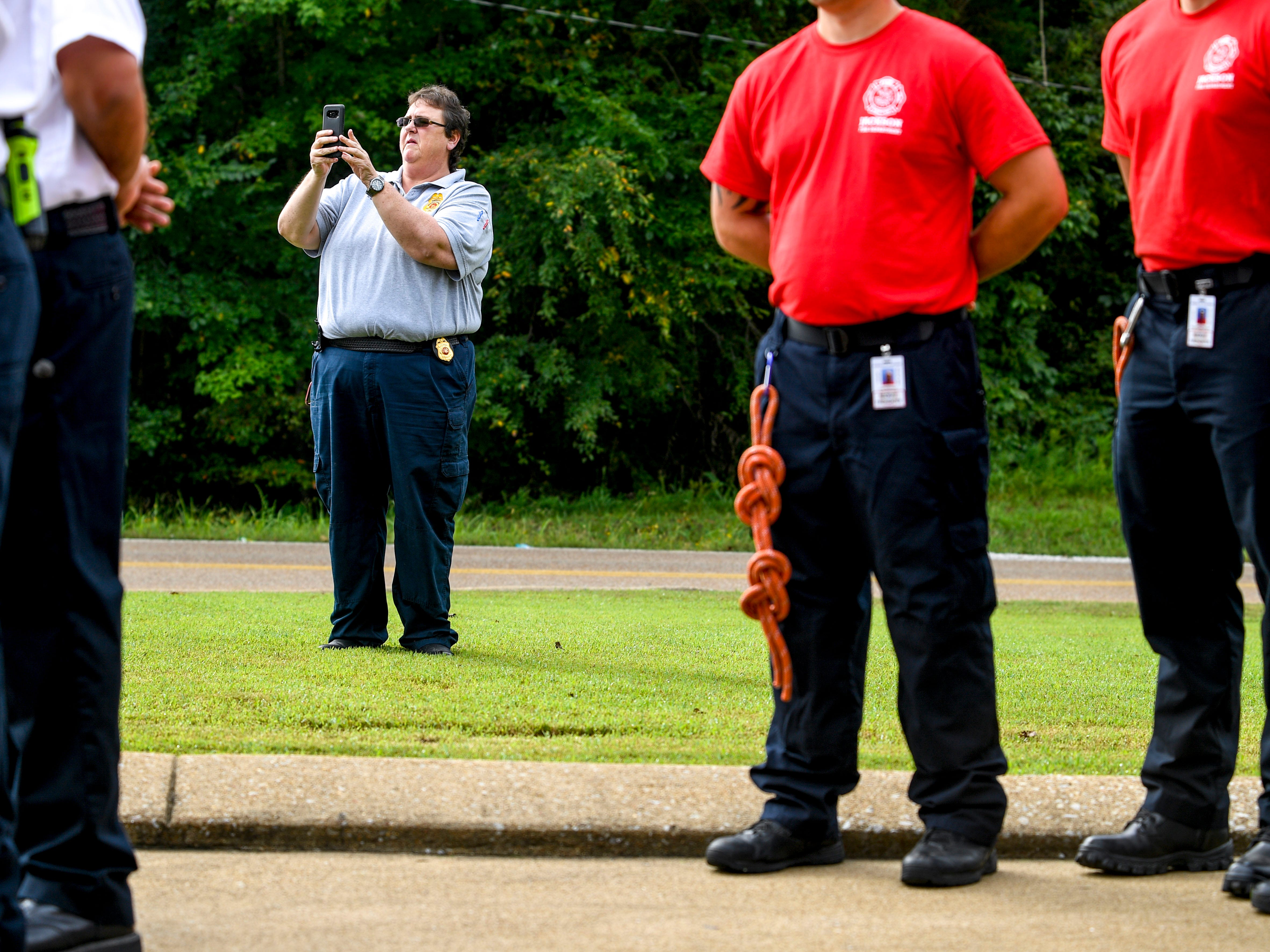 Tina Curtis, a fire investigator, takes photos of the event during a ceremony honoring the victims of the 9/11 attacks at Fire Station 3 in Jackson, Tenn., on Tuesday, Sept. 11, 2018.