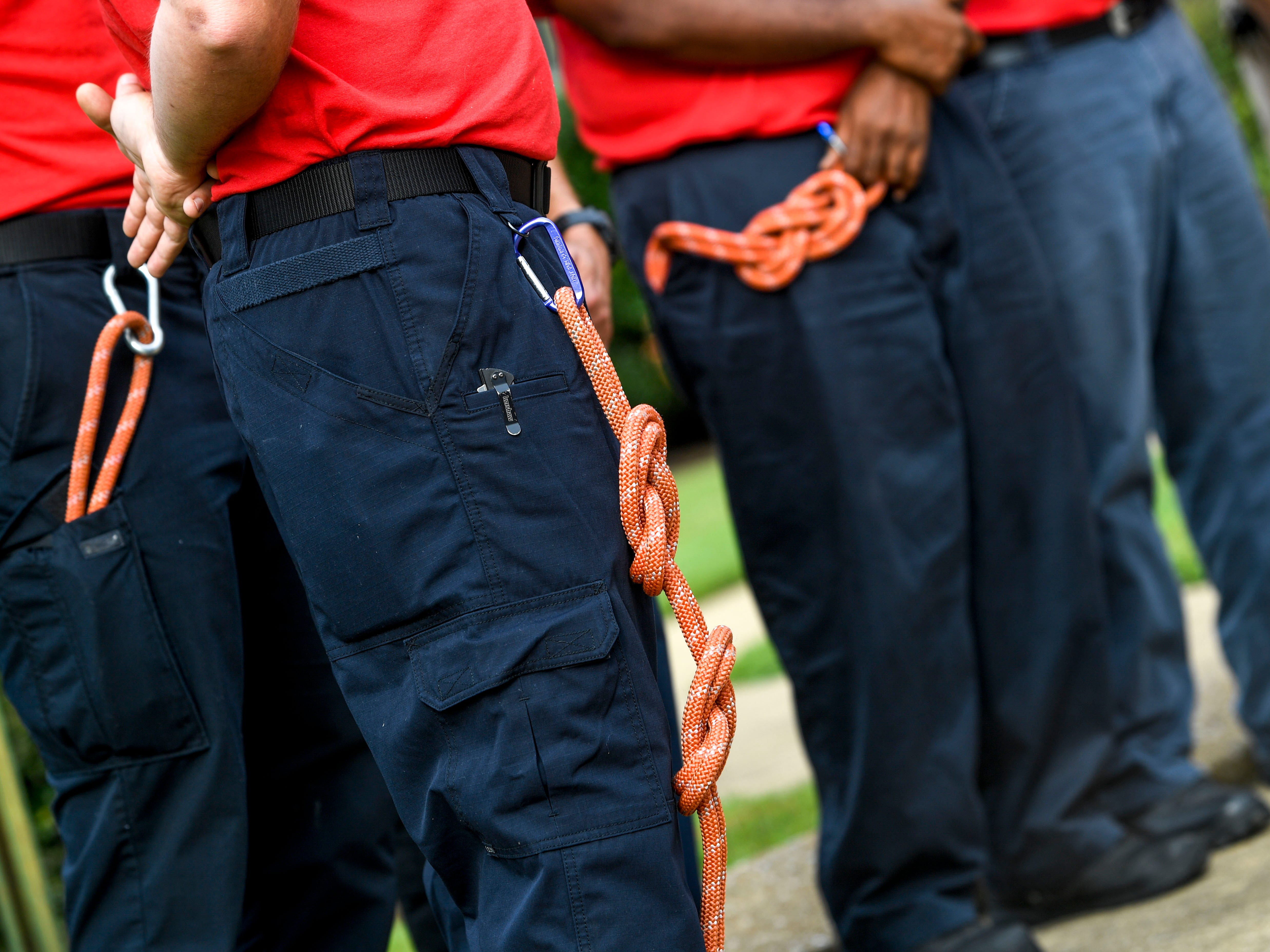 Recruits to the Jackson Fire Department stand at attention with ropes they are assigned to learn how to tie knots hanging from their belts during a ceremony honoring the victims of the 9/11 attacks at Fire Station 3 in Jackson, Tenn., on Tuesday, Sept. 11, 2018.