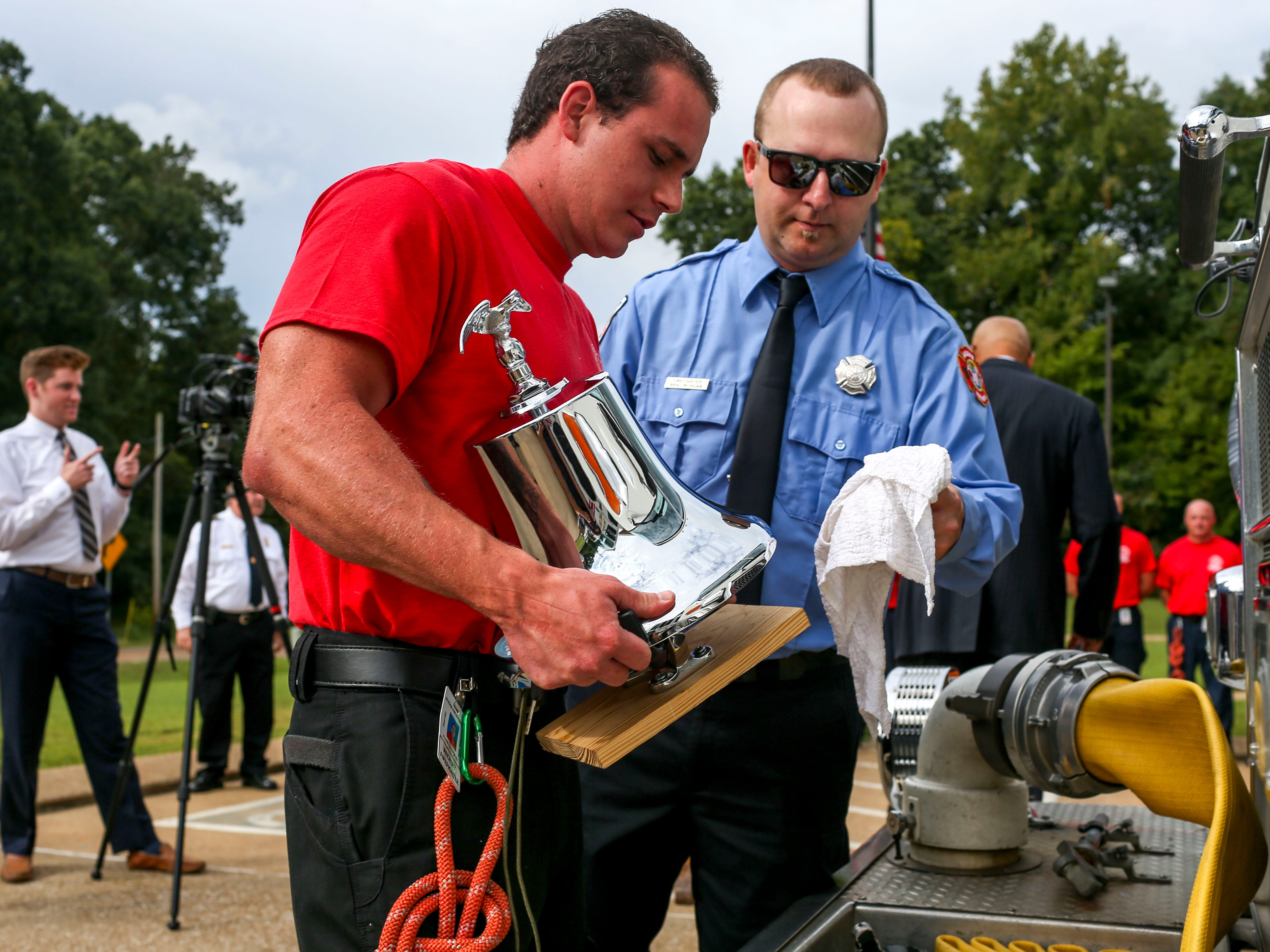 Brad Morgan, right, assists new recruit Hunter Wells, left, put away the ceremonial bell after an event honoring the victims of the 9/11 attacks at Fire Station 3 in Jackson, Tenn., on Tuesday, Sept. 11, 2018.