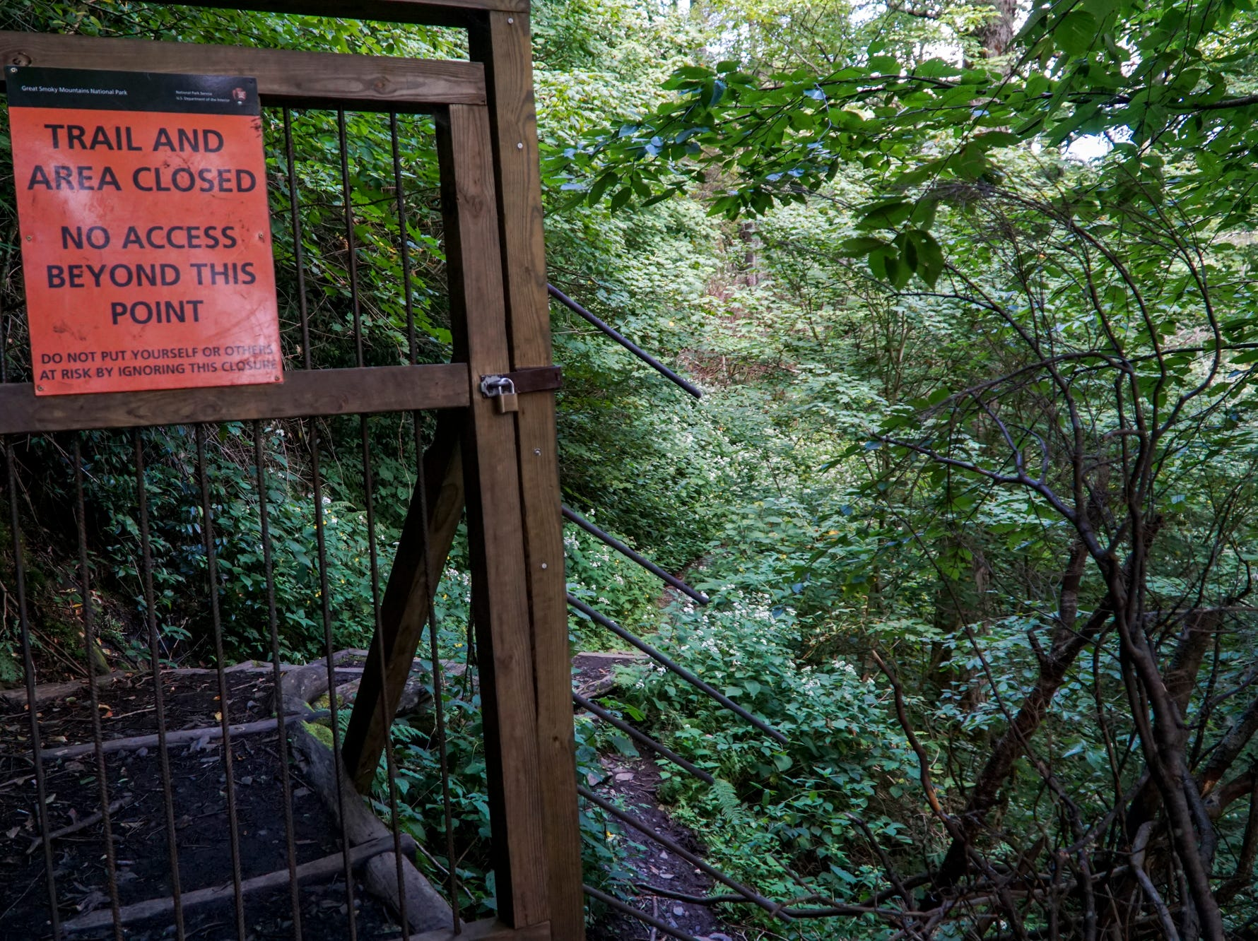 A wood and metal gate prevents hikers from accessing the previous peak of the Chimney Tops trail which was damaged by the Chimney Tops 2 fire in 2016.