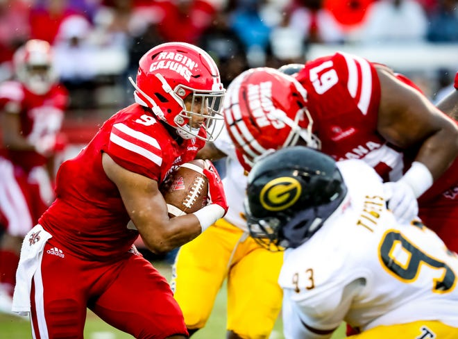 UL left guard Ken Marks (67) blocks in the background as running back Trey Ragas (9) gains some of his 142 yards in a season-opening win over Grambling.
