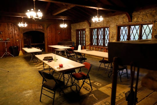 Mambourg Lodge's main room features detailed wooden arches and walls, a stone fireplace and wall and a shuffleboard floor.